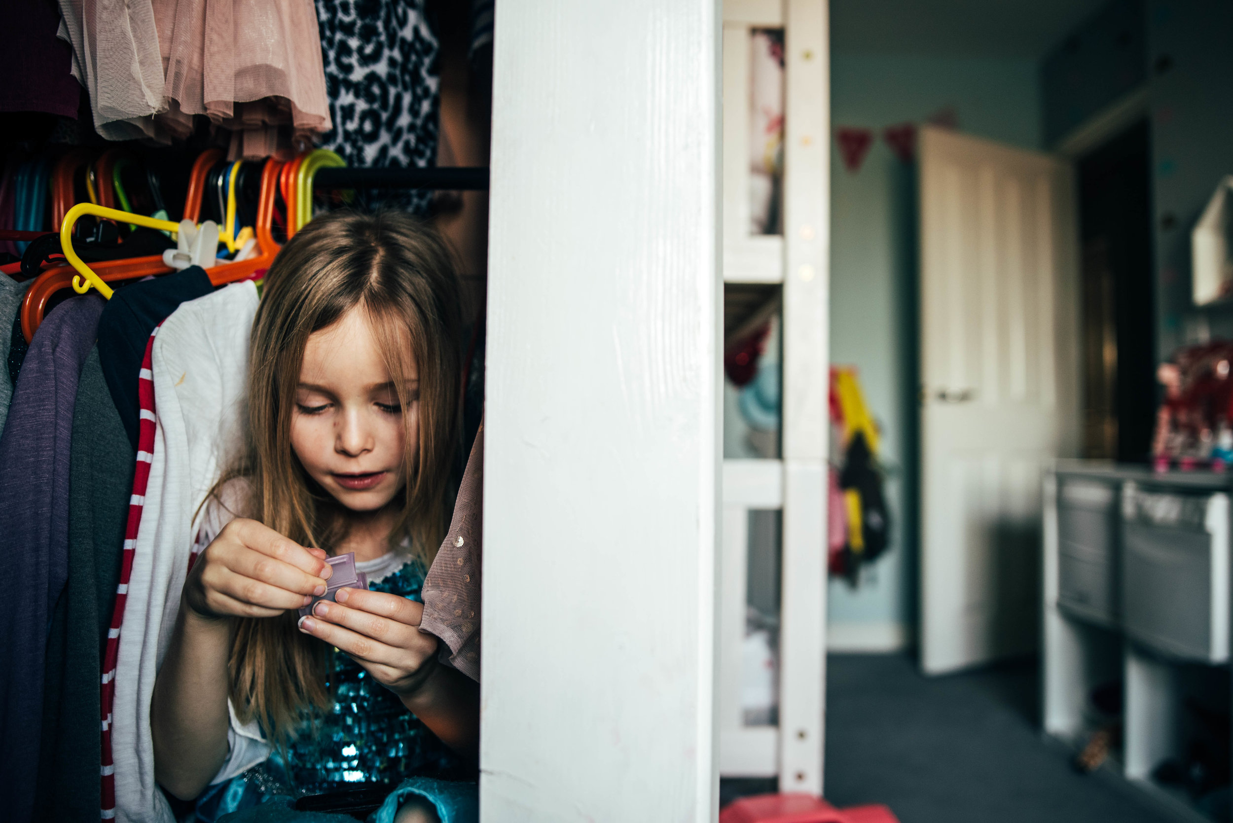young girl plays in her wardrobe Essex UK family childhood documentary photographer