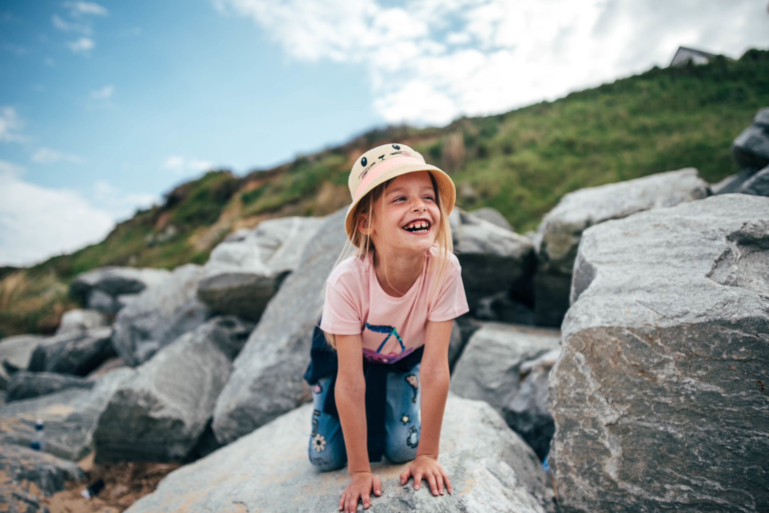 little girl on rocky beach in sunhat Essex UK Documentary Lifestyle Portrait Photographerw