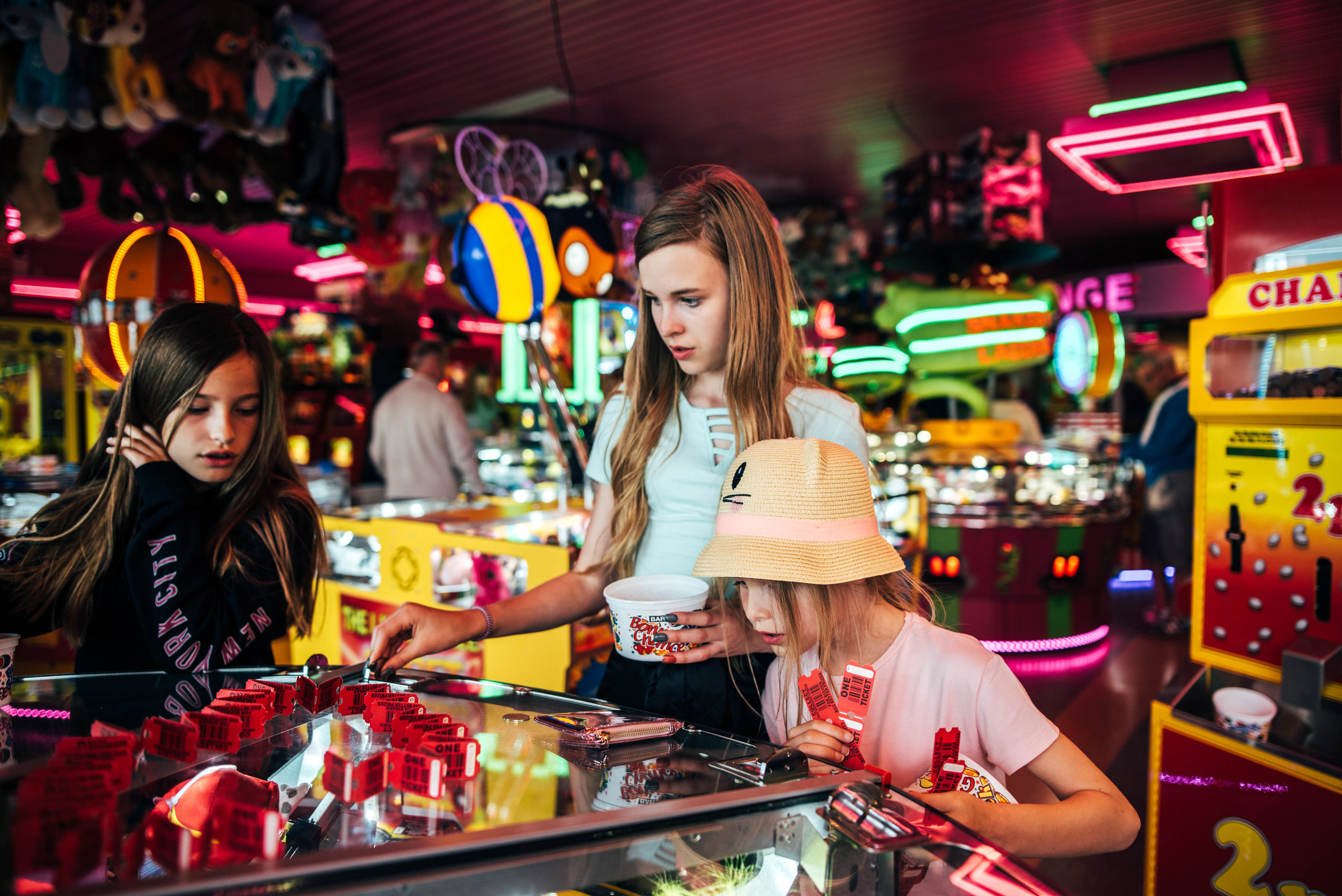 Three girls in amusement arcade penny slots Essex UK Documentary Lifestyle Portrait Photographer