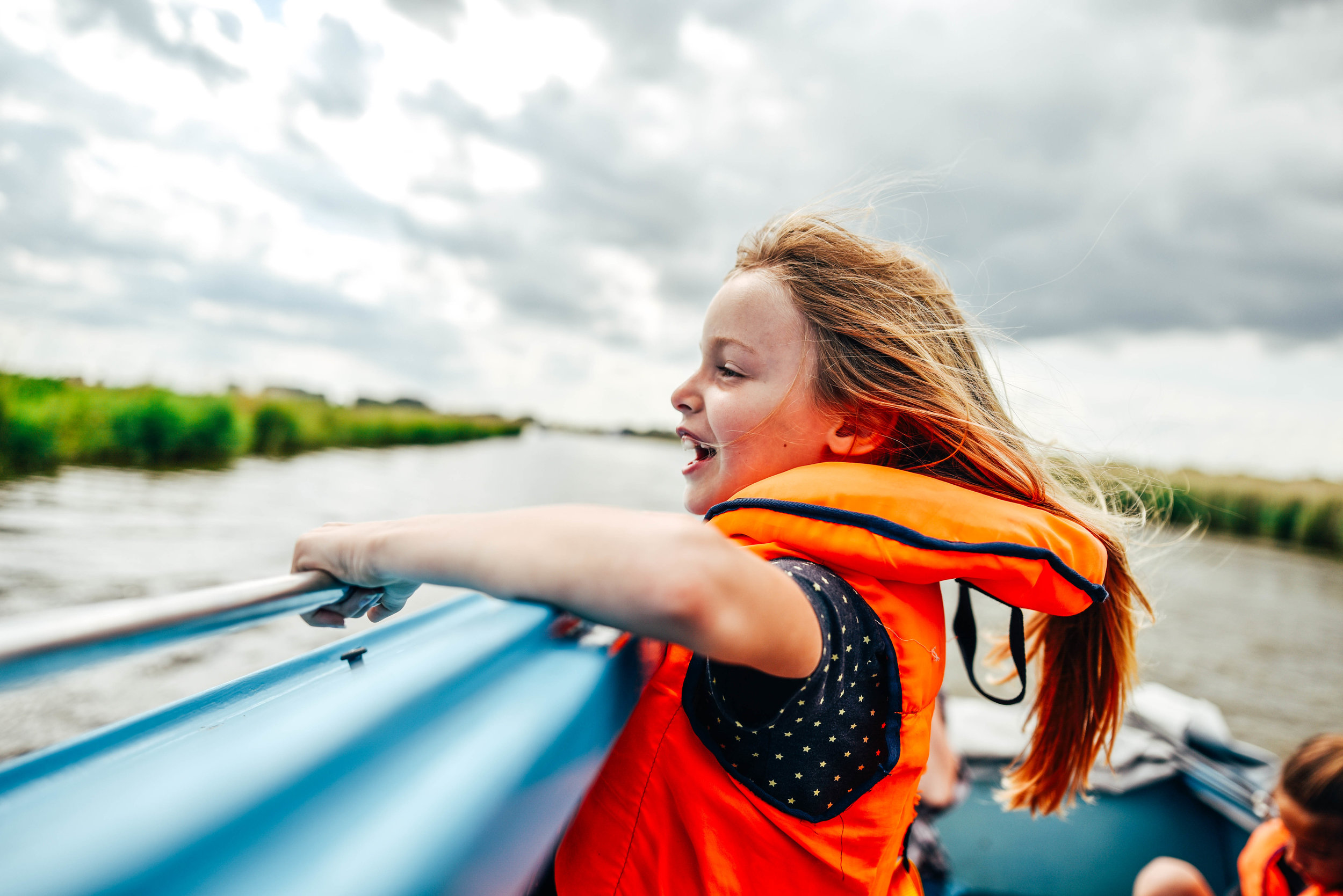 Little girl in life jacket on river boat Essex UK Documentary Lifestyle Portrait Photographer