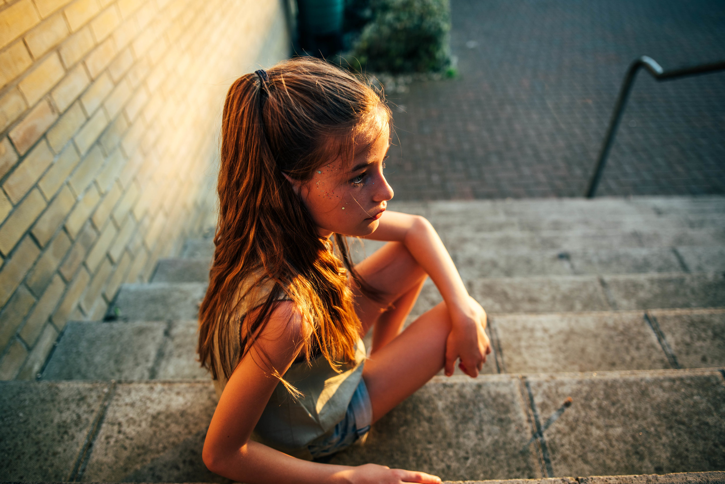 Young girl sits on steps in sunset Essex UK Documentary Portrait Photographer