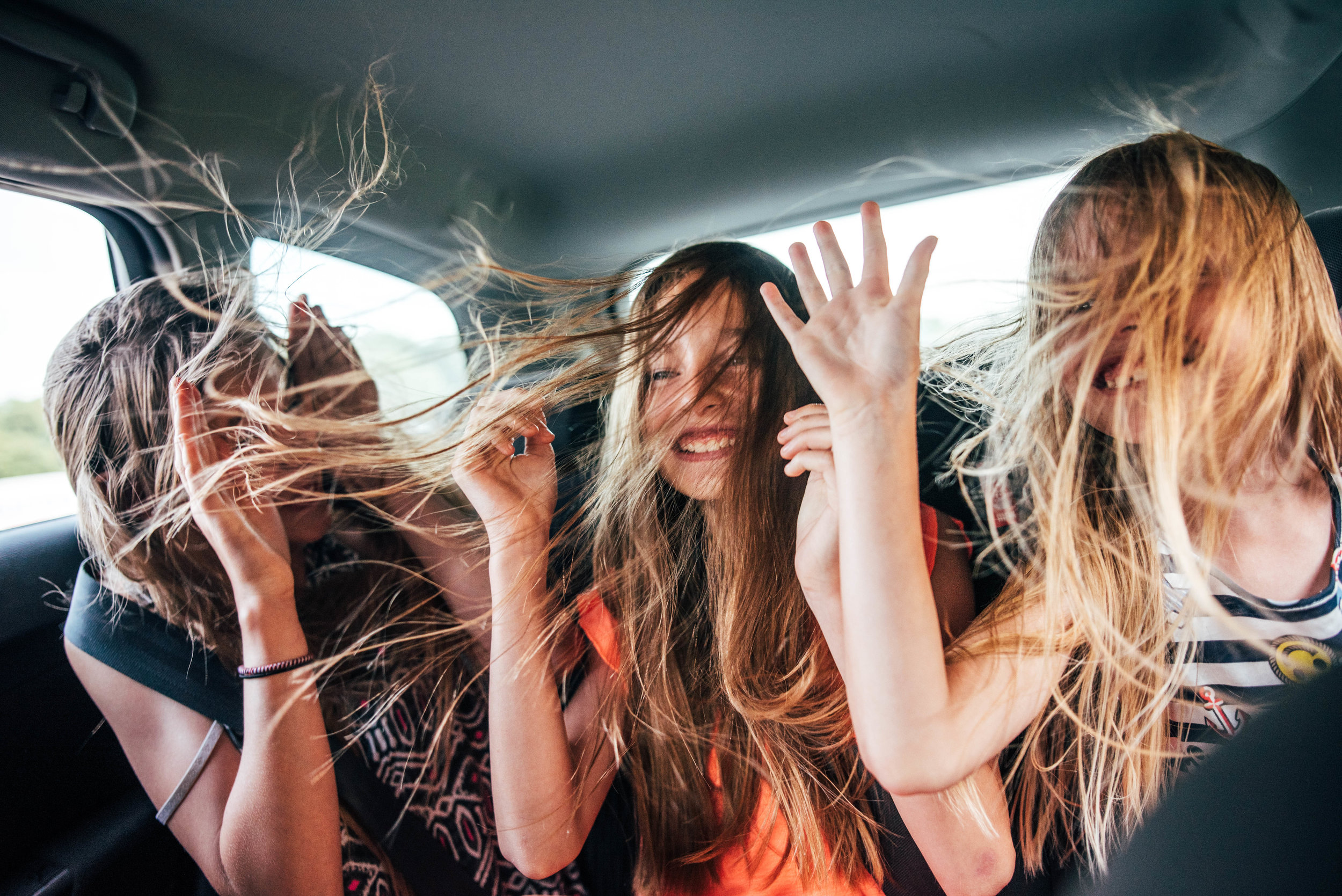 Three girls in back of a car with windows down, hair blowing Essex UK Documentary Portrait Photographer