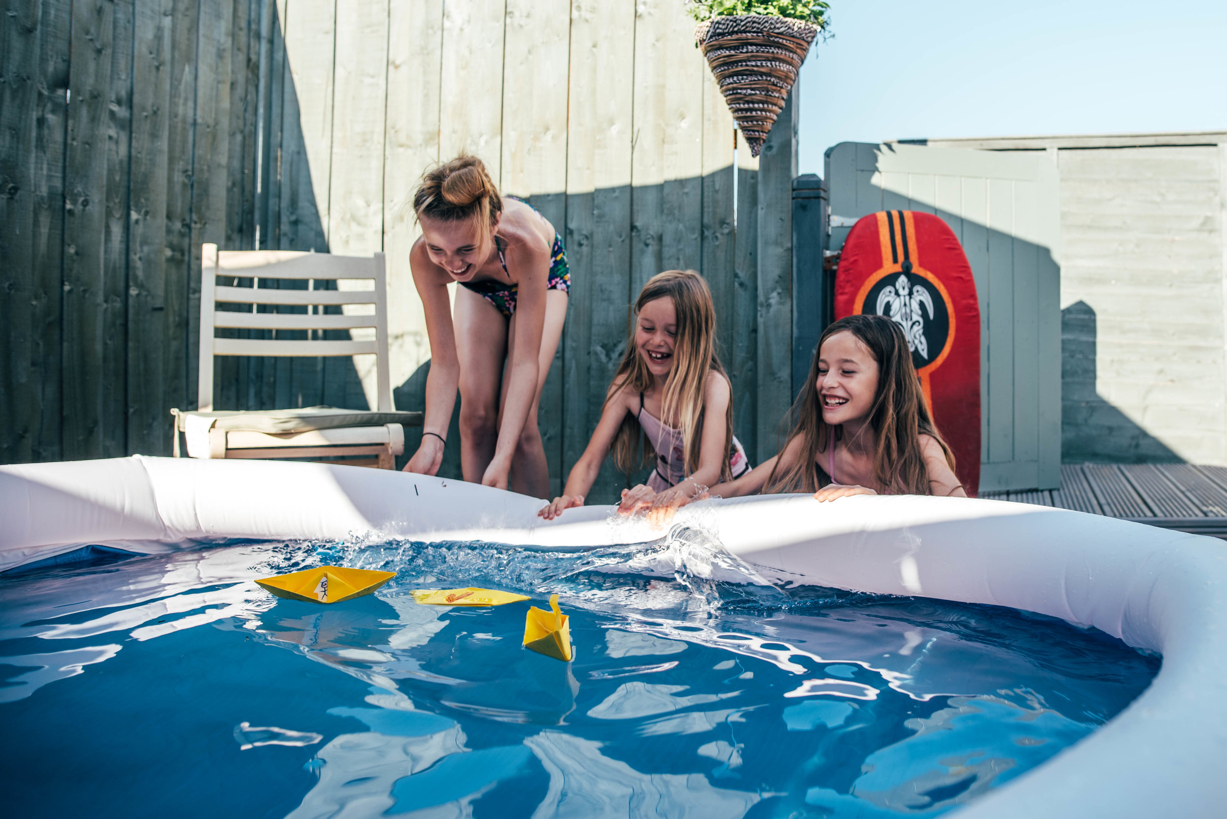 Three girls race paper boats in pool Essex UK Documentary Portrait photographer