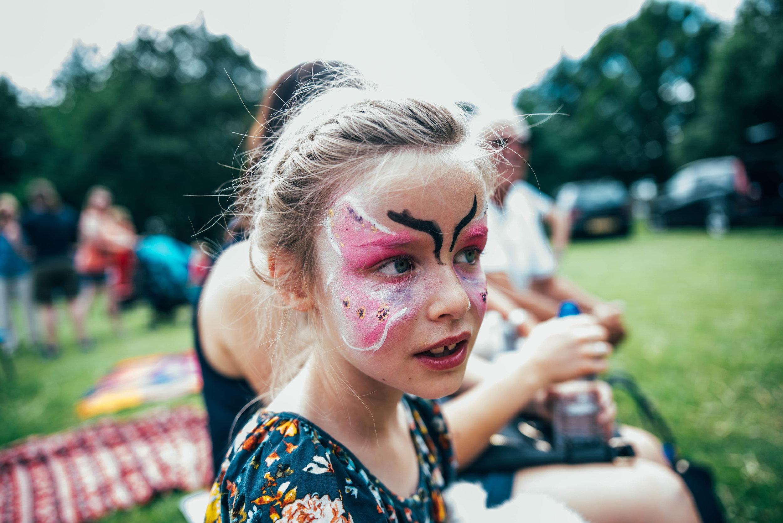 Young girl with butterfly face paint at festival Essex UK Documentary Portrait Photographer