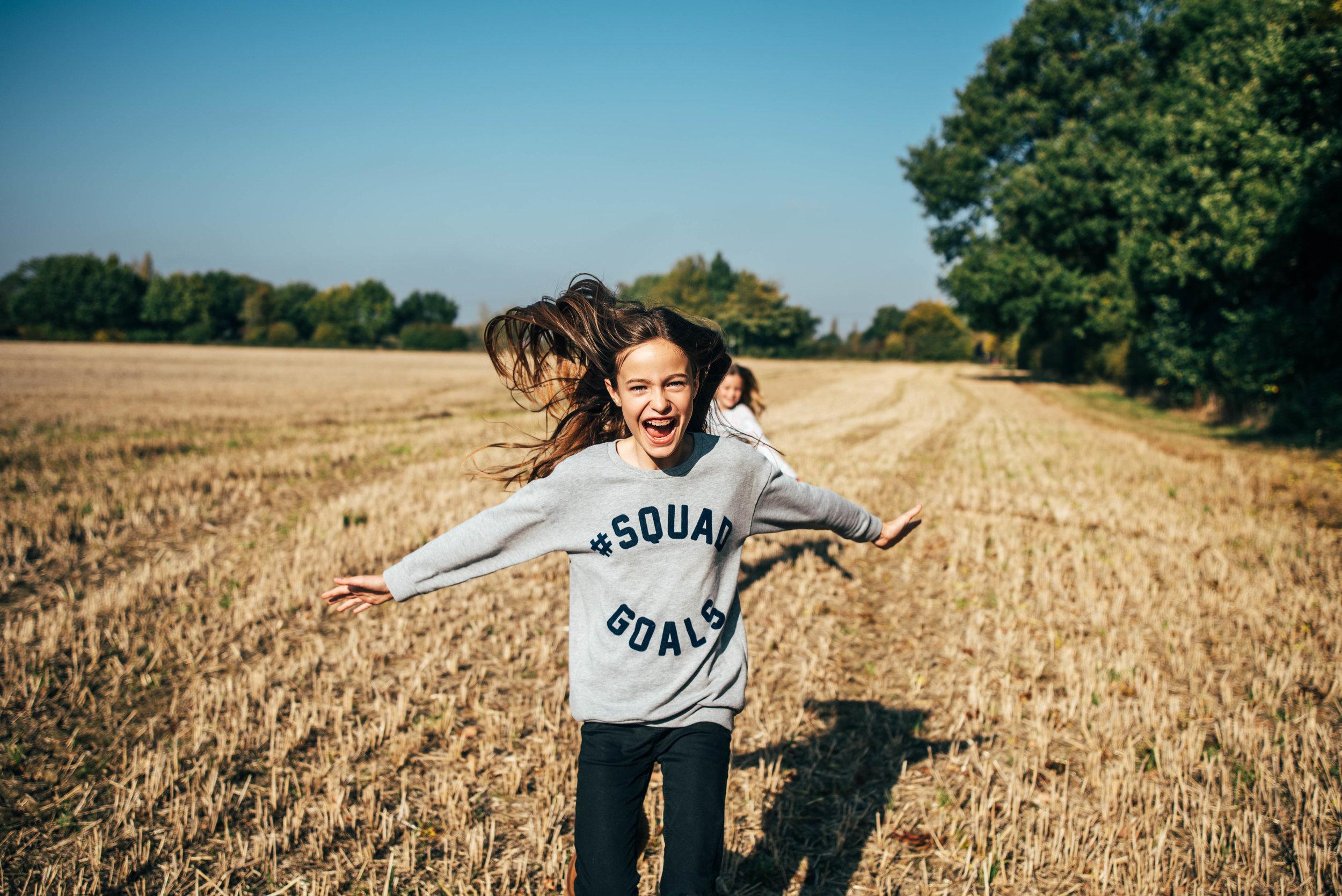 Tween girl running in Autumn field Essex UK Documentary Wedding Photographer