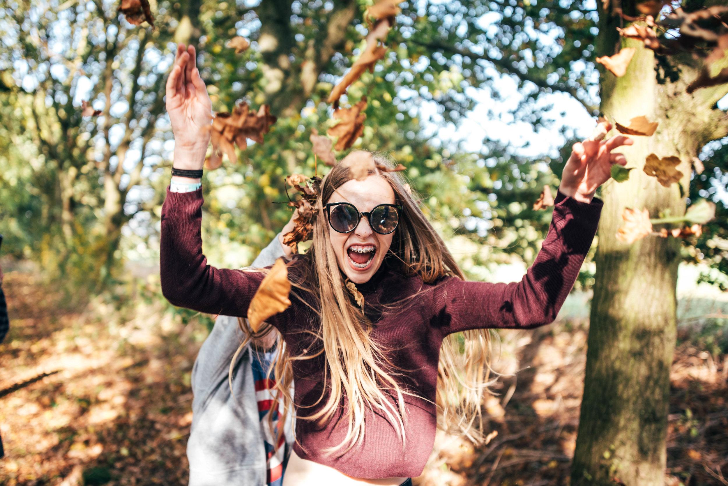 Teen girl throwing autumn leaves Essex UK Documentary Wedding Photographer