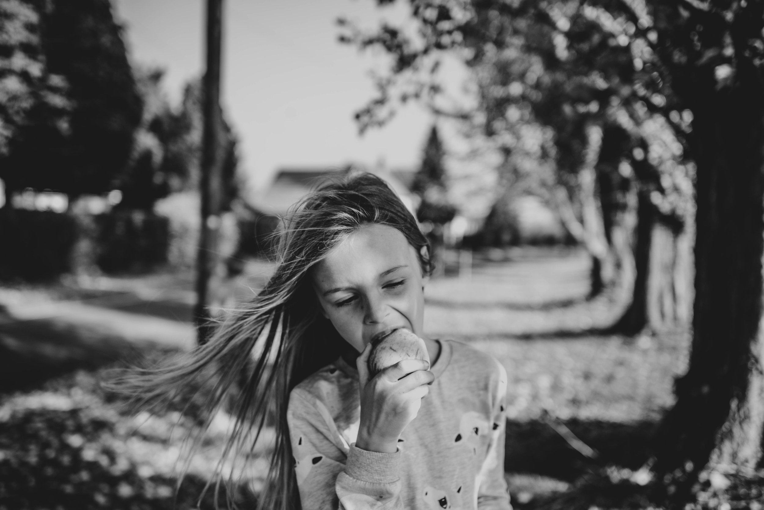 Young girl eats apple from tree Essex UK Documentary Wedding Photographer