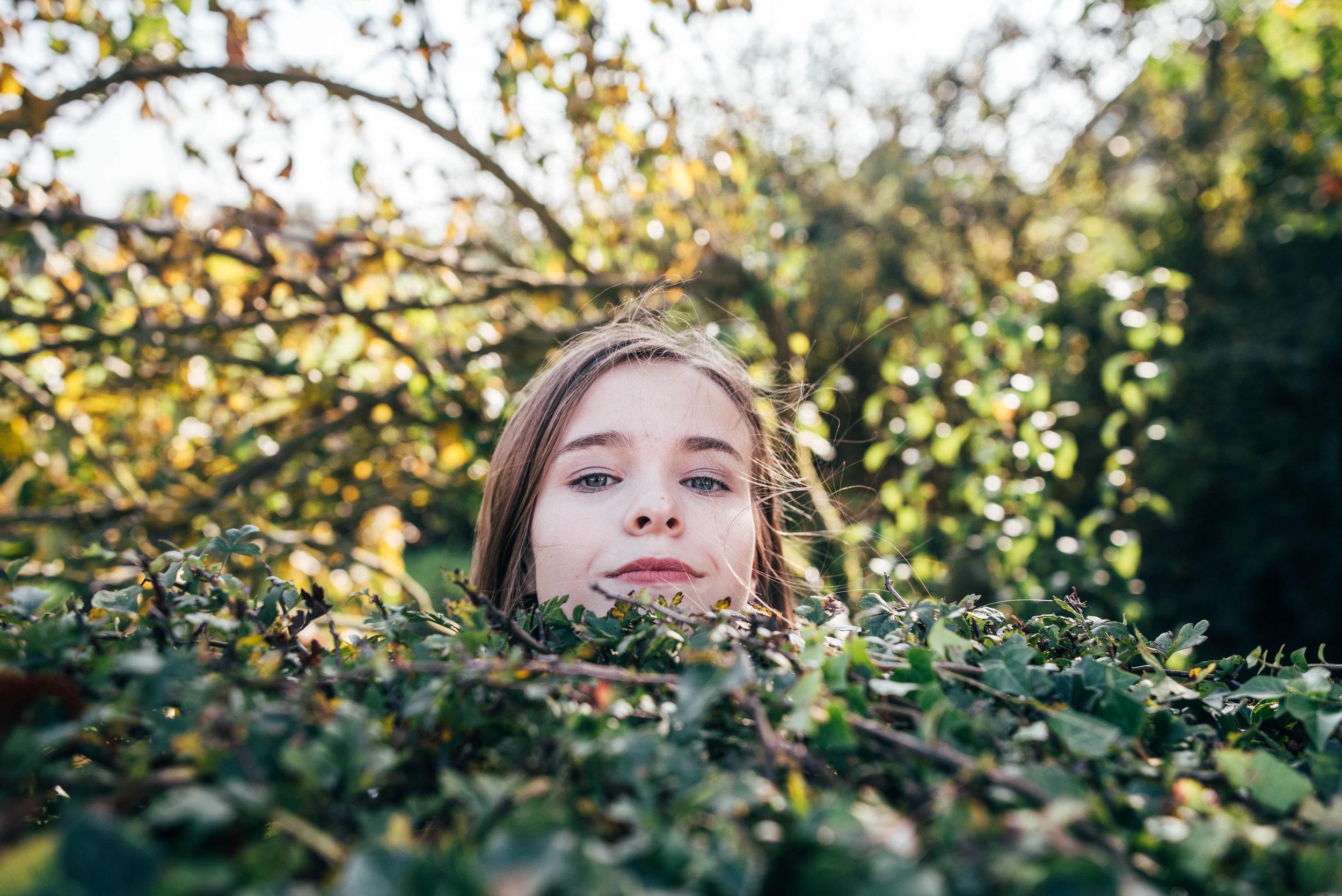 Teen girl peers over hedge Essex UK Documentary Wedding Photographer