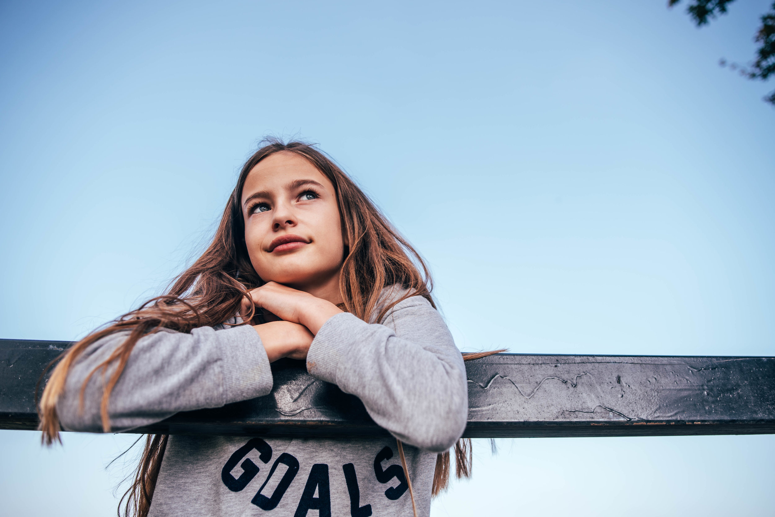 Tween girl leans on fence Essex UK Documentary Wedding Photographer