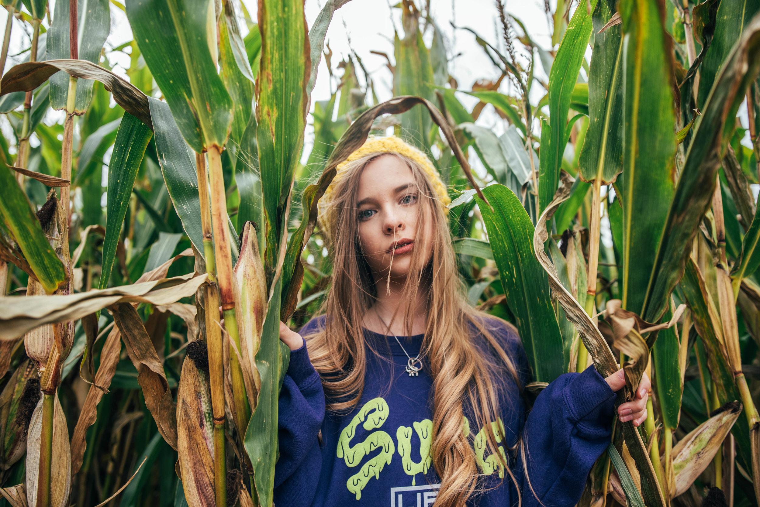 Teen girl in Sugg Life jumper stands in cornfield Essex UK Documentary Wedding Photographer