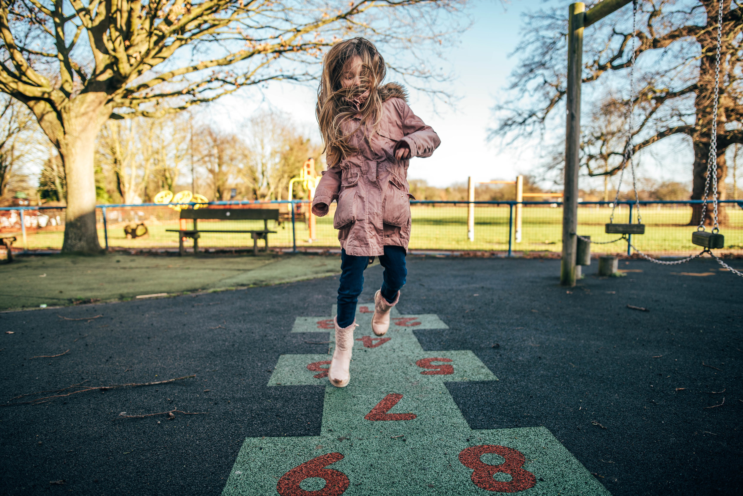 Girl plays hopscotch in winter park Essex UK Wedding Documentary Photographer