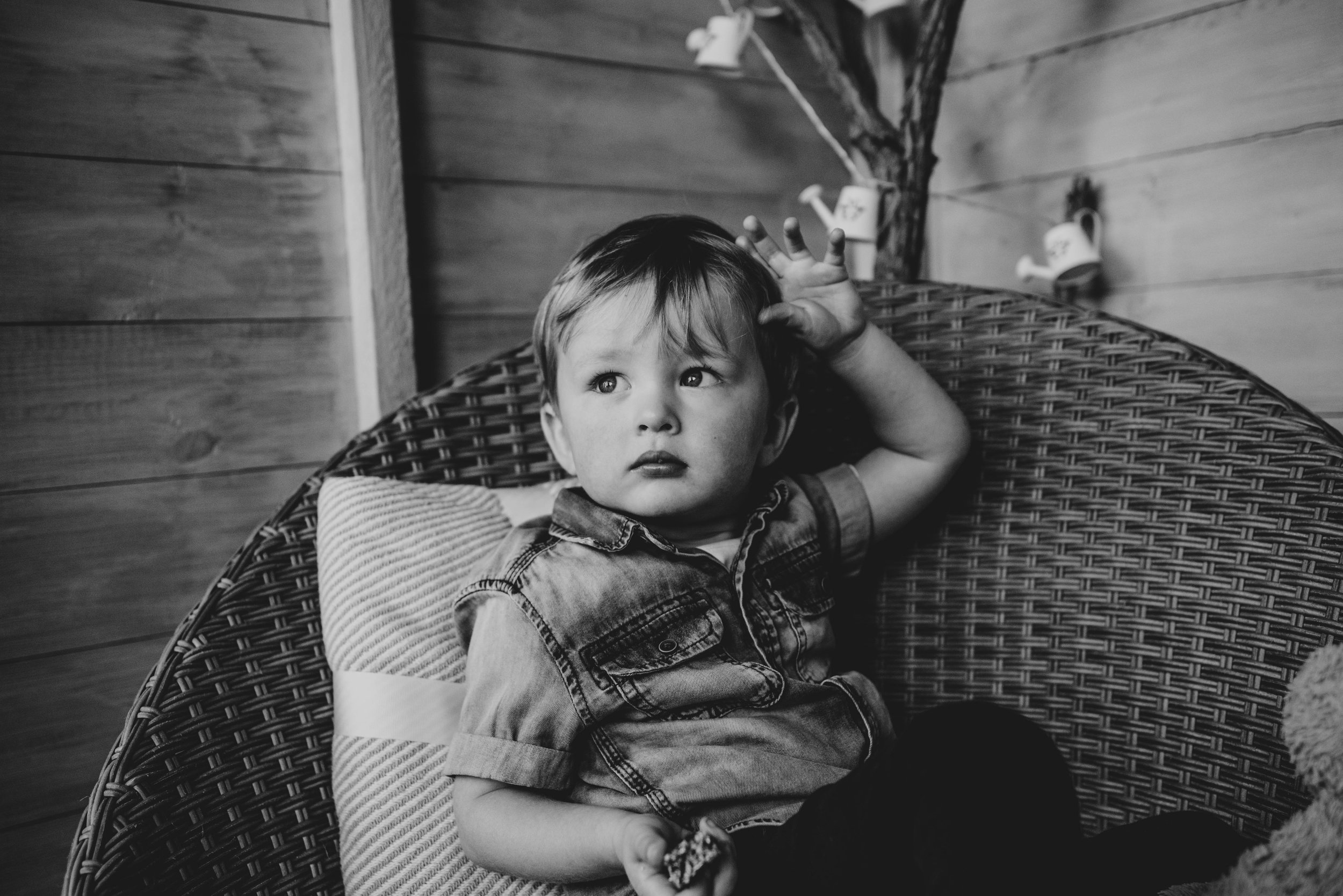 Toddler boy sits in chair in Shed Essex Documentary Portrait Photographer