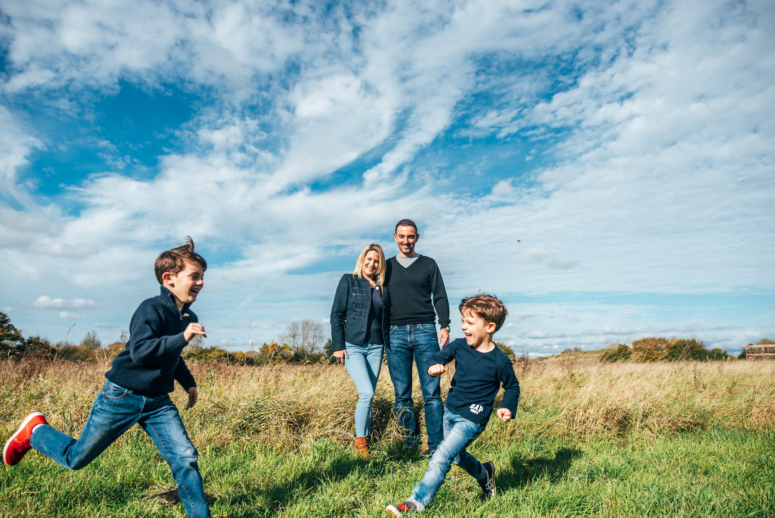 Young boys run in field Essex Documentary Portrait Photographer