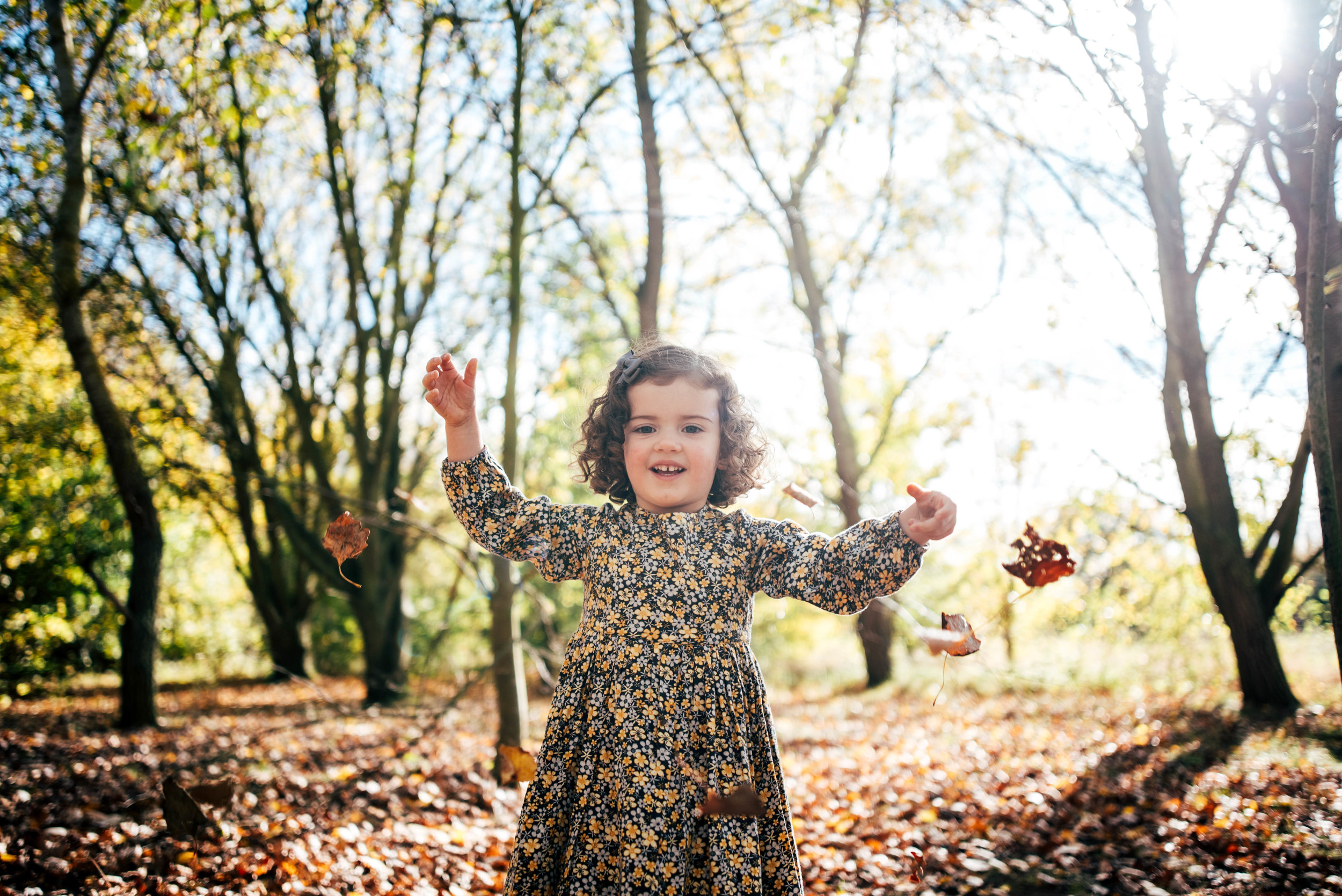 Little girl throws autumn leaves Essex Documentary Portrait Photographer