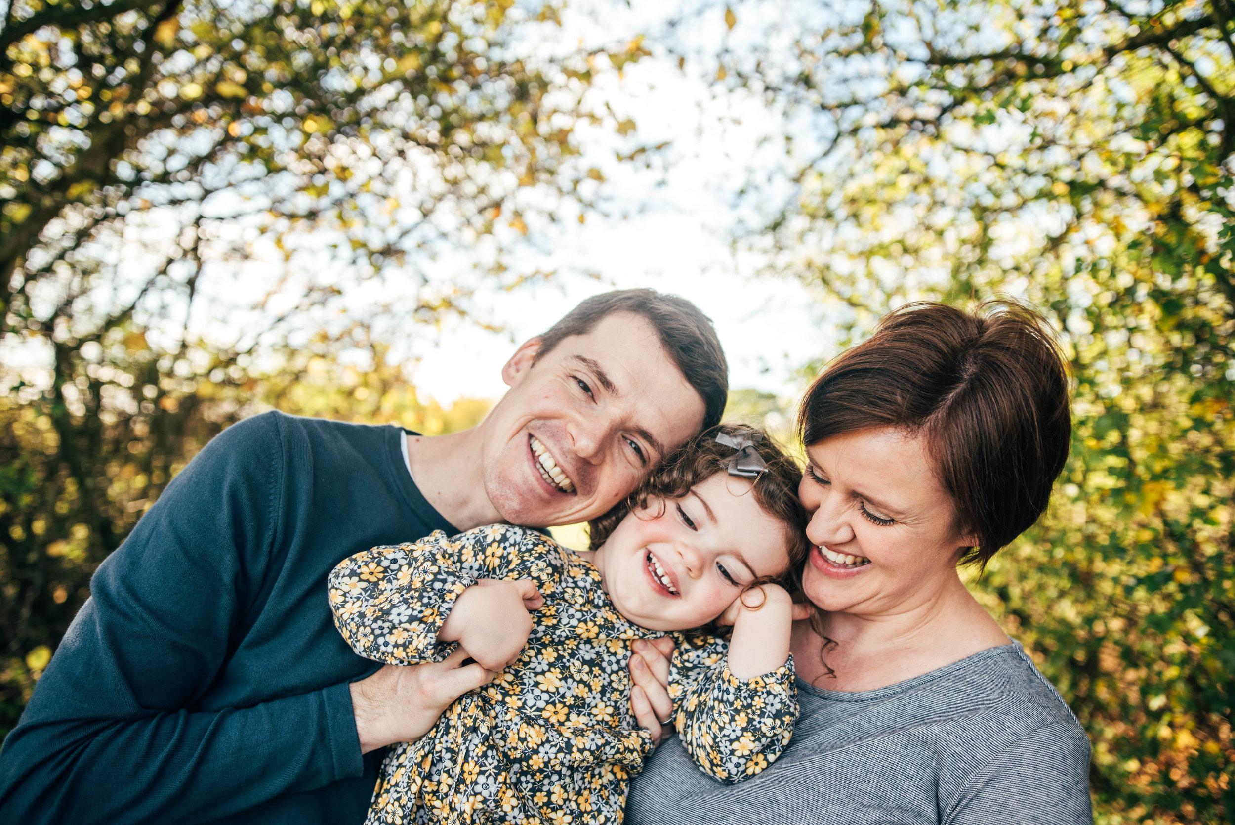 Mum and Dad hug little girl autumn Essex Documentary Portrait Photographer