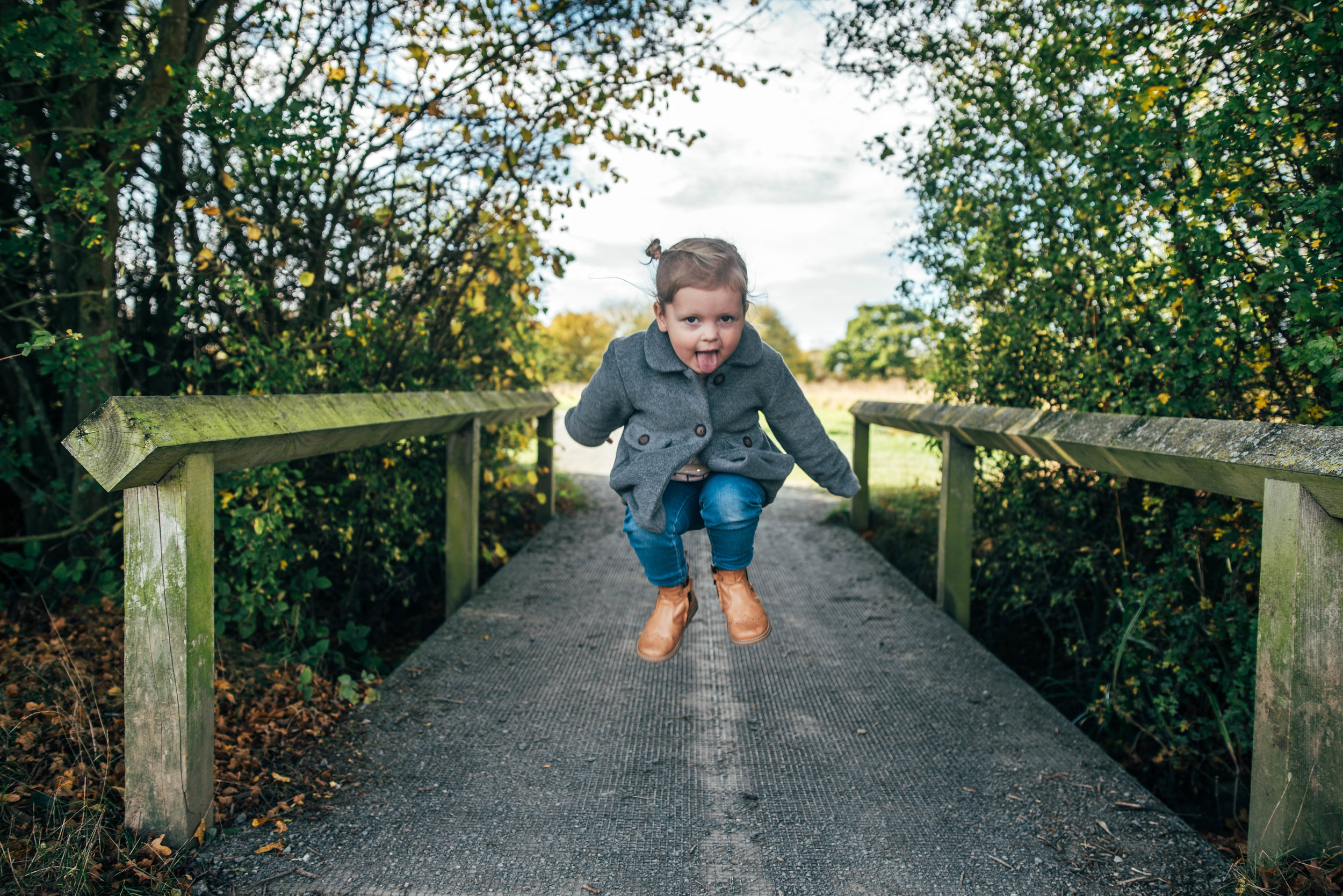 Little girl jumps on bridge Essex Documentary Portrait Photographer