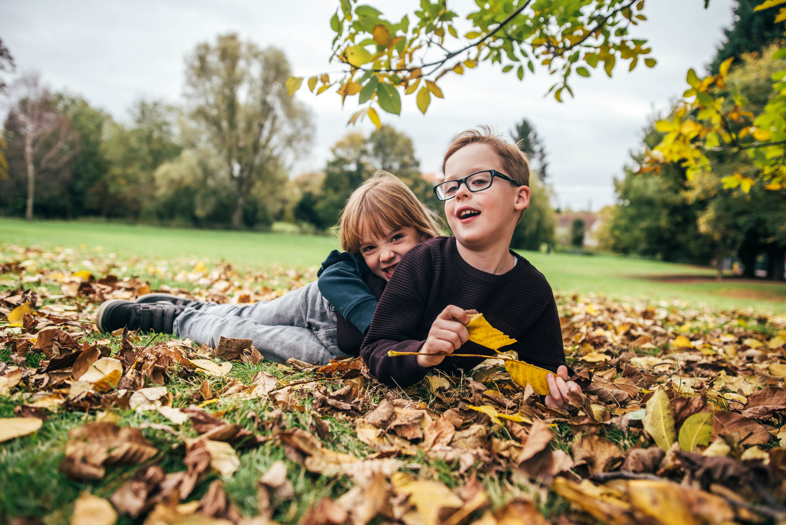 Brother and Sister play in autumn leaves Essex Documentary Portrait Photographer