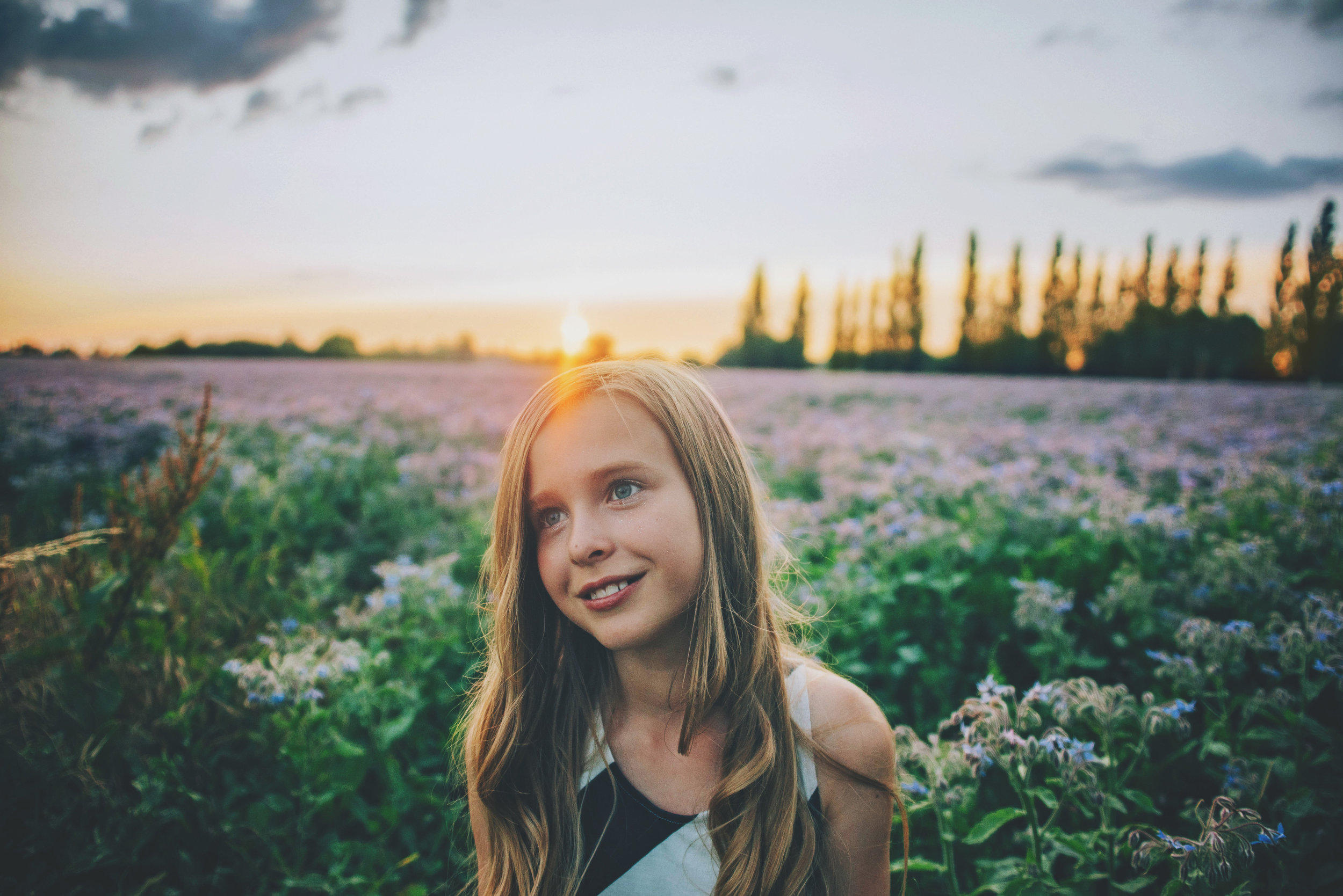 Tween girl sits in purple field at sunset Essex Documentary Portrait Photographer