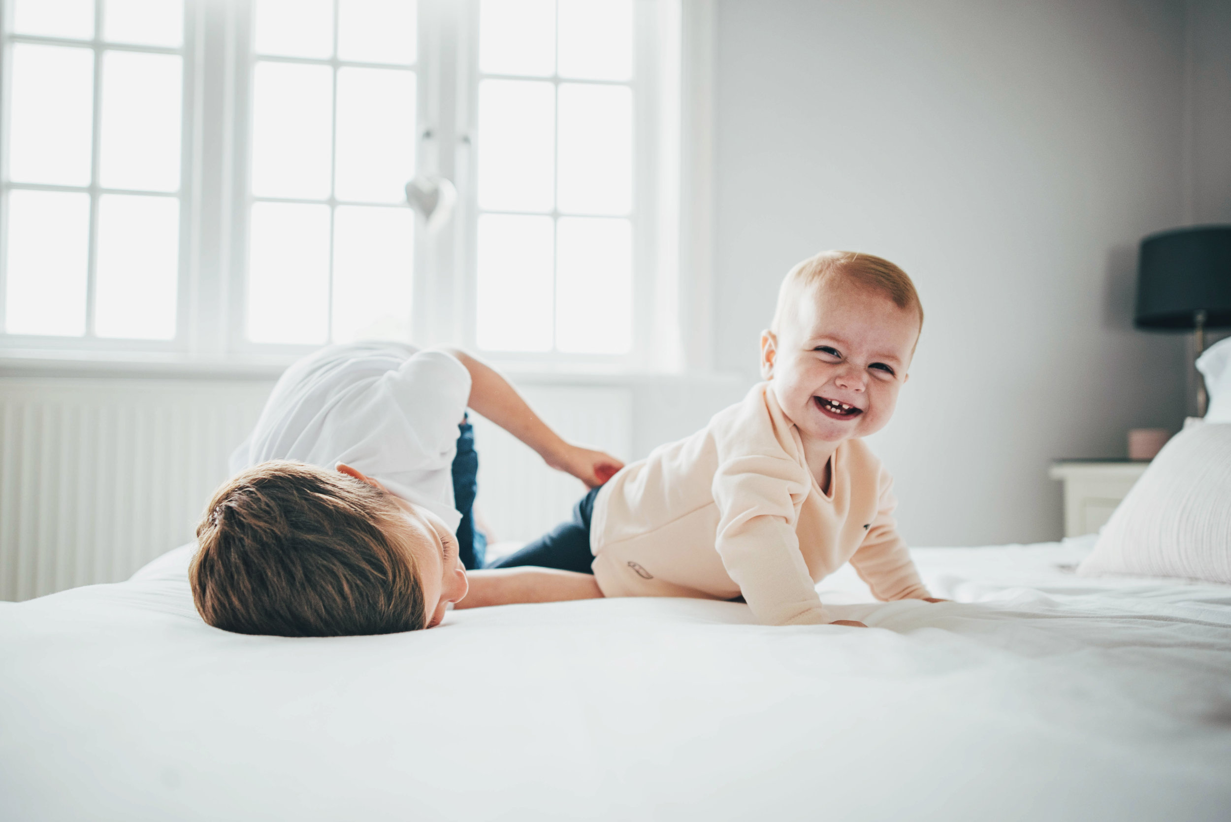 Brother and sister play on bed Essex Documentary Portrait Photographer