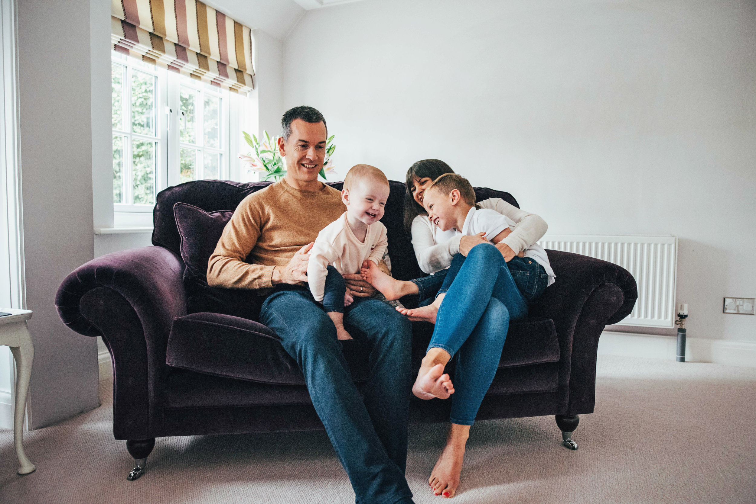 Family cuddle on sofa Essex Documentary Portrait Photographer
