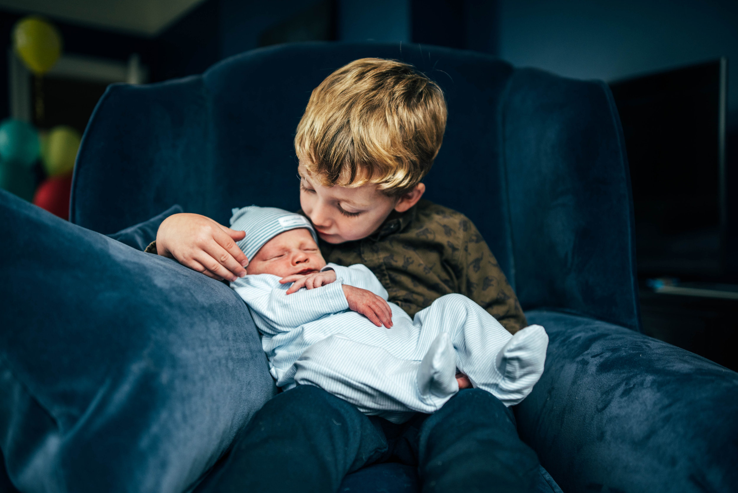 Boy holds baby brother Essex Documentary Portrait Photographer