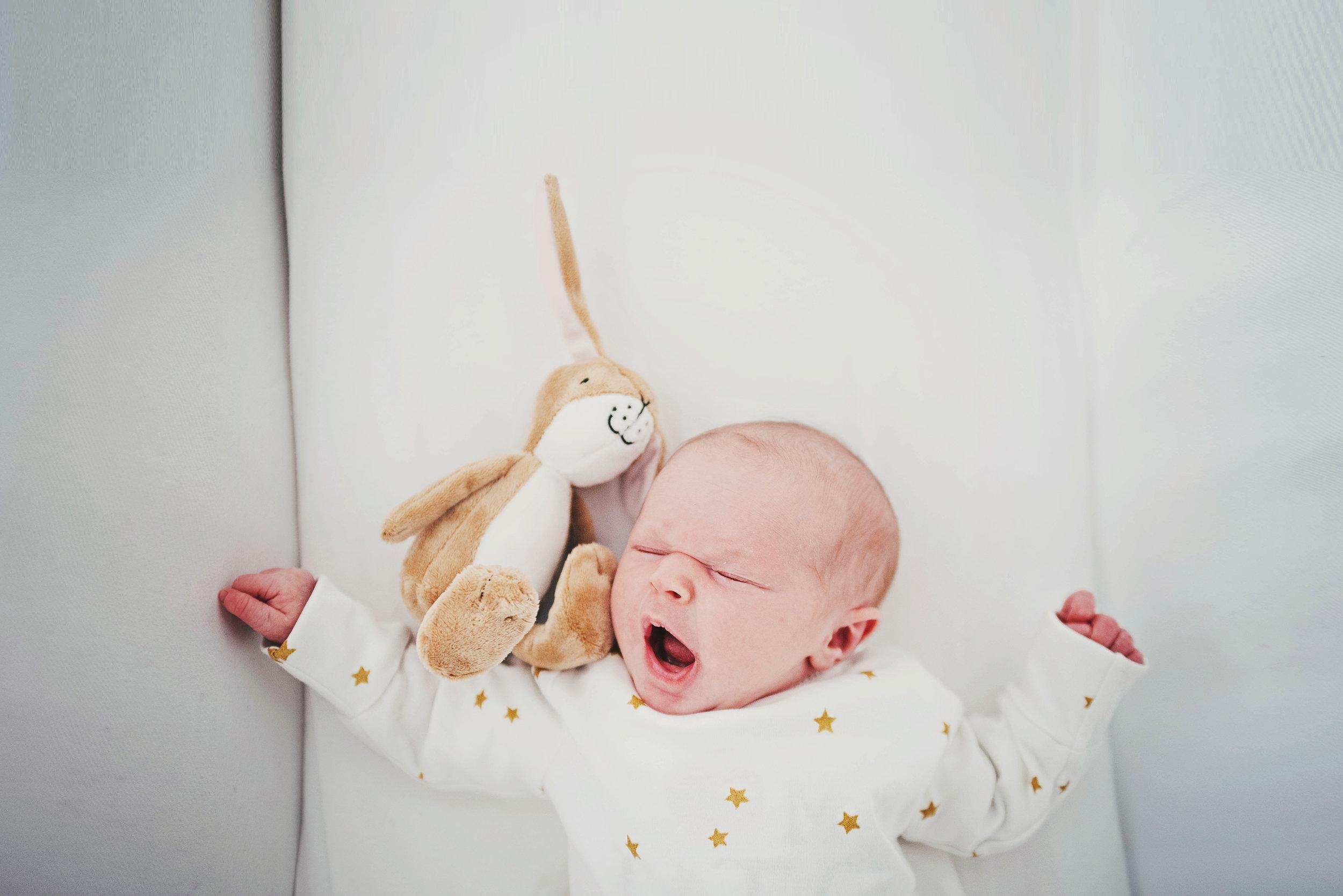 Newborn baby yawns in crib essex Documentary Portrait photographer
