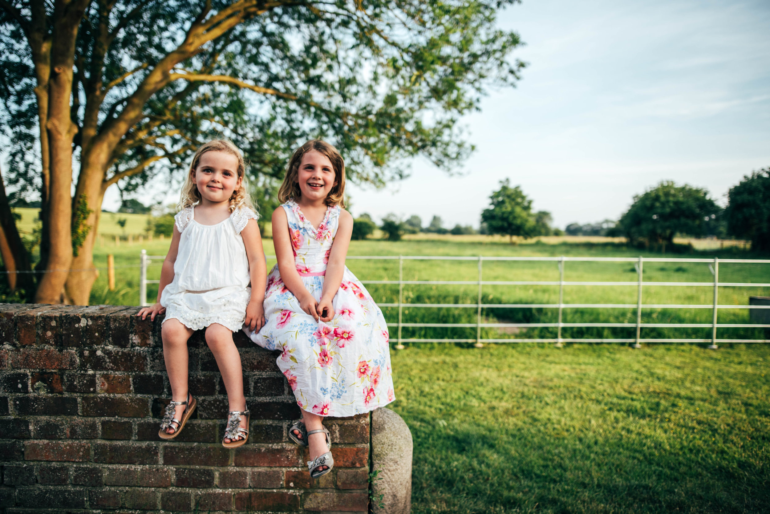 two sisters sit on wall Essex Documentary Portrait Photographer