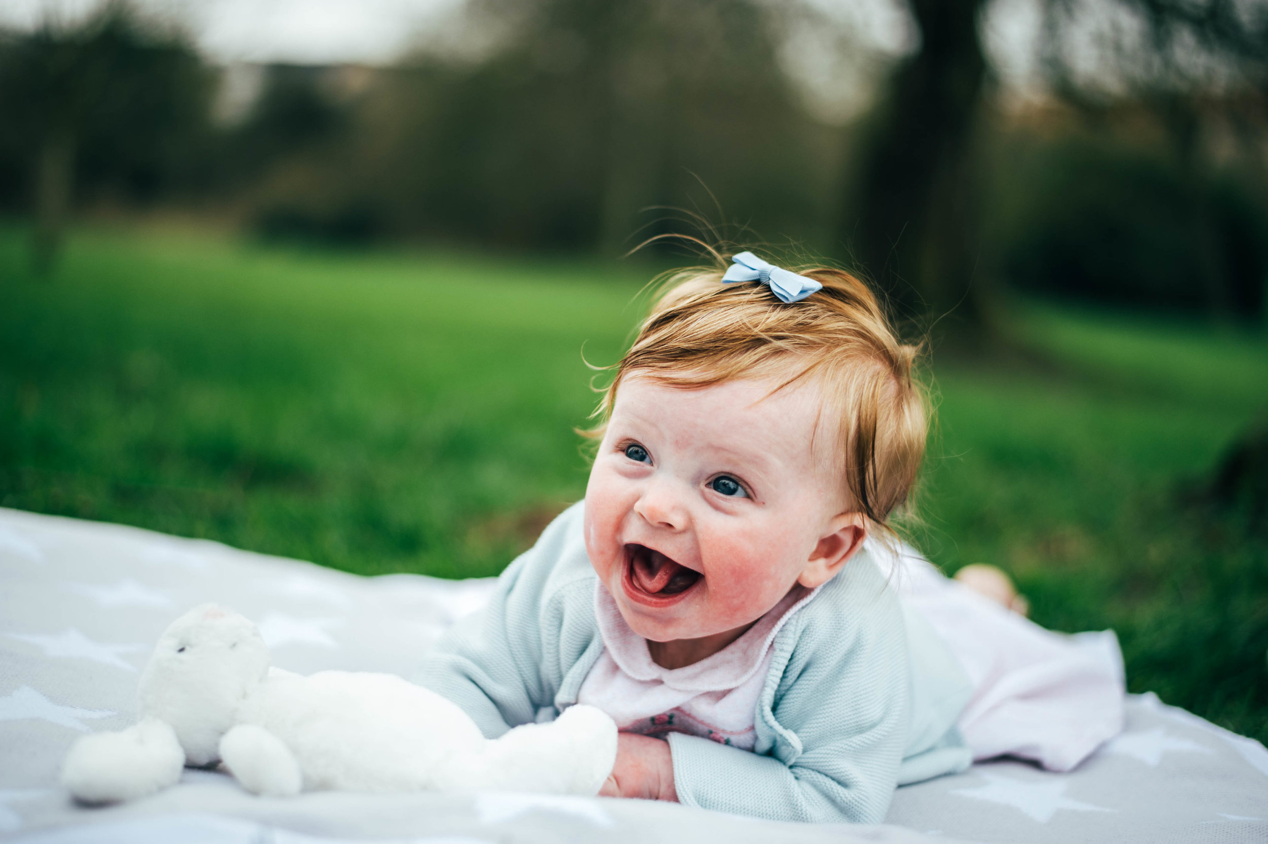 baby girl laughs on blanket Essex documentary portrait photographer