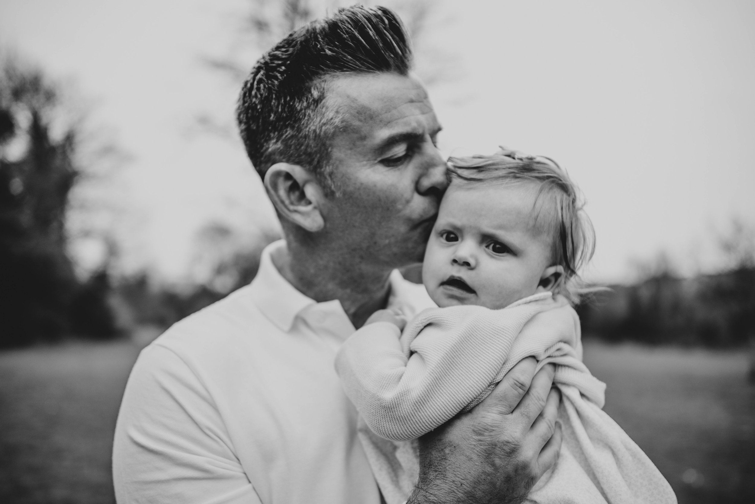 Dad kisses baby girl Essex Documentary Portrait Photographer