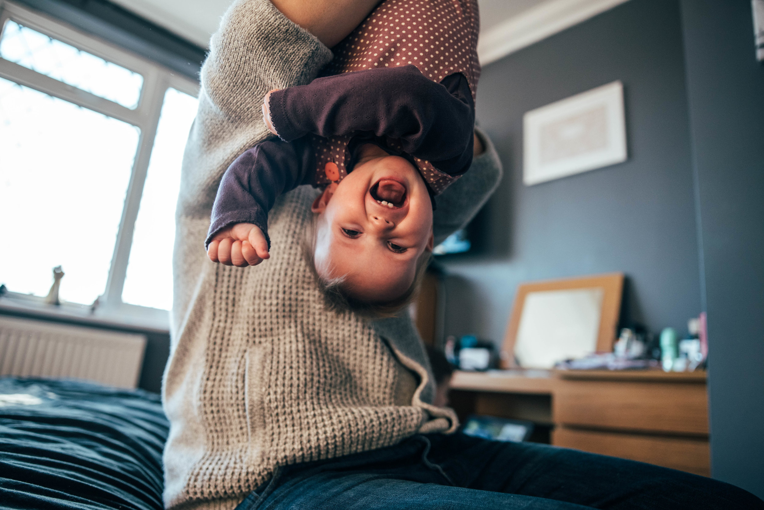 dad holds baby girl upside down essex documentary portrait photographer