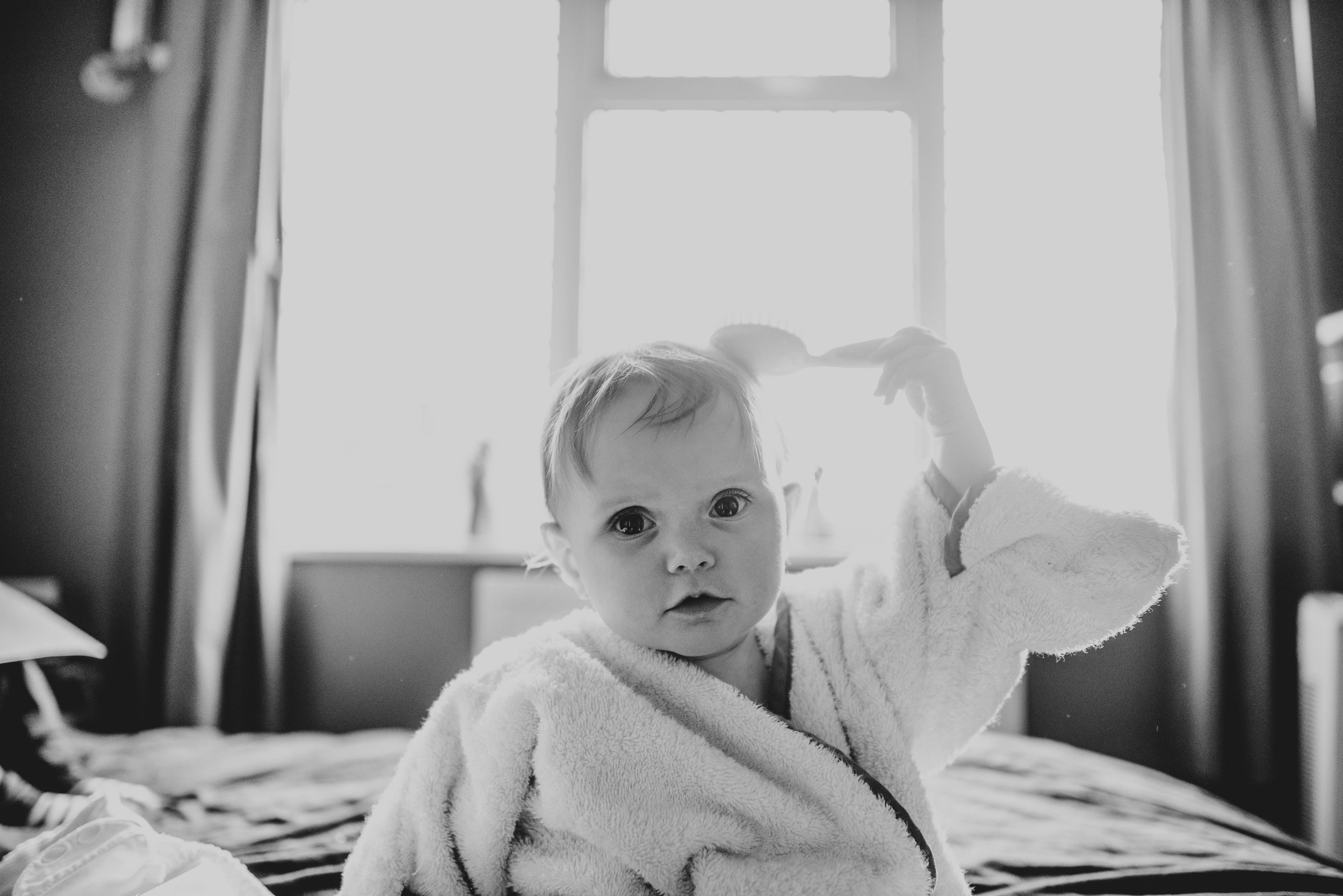 baby brushes hair on bed essex documentary portrait photographer