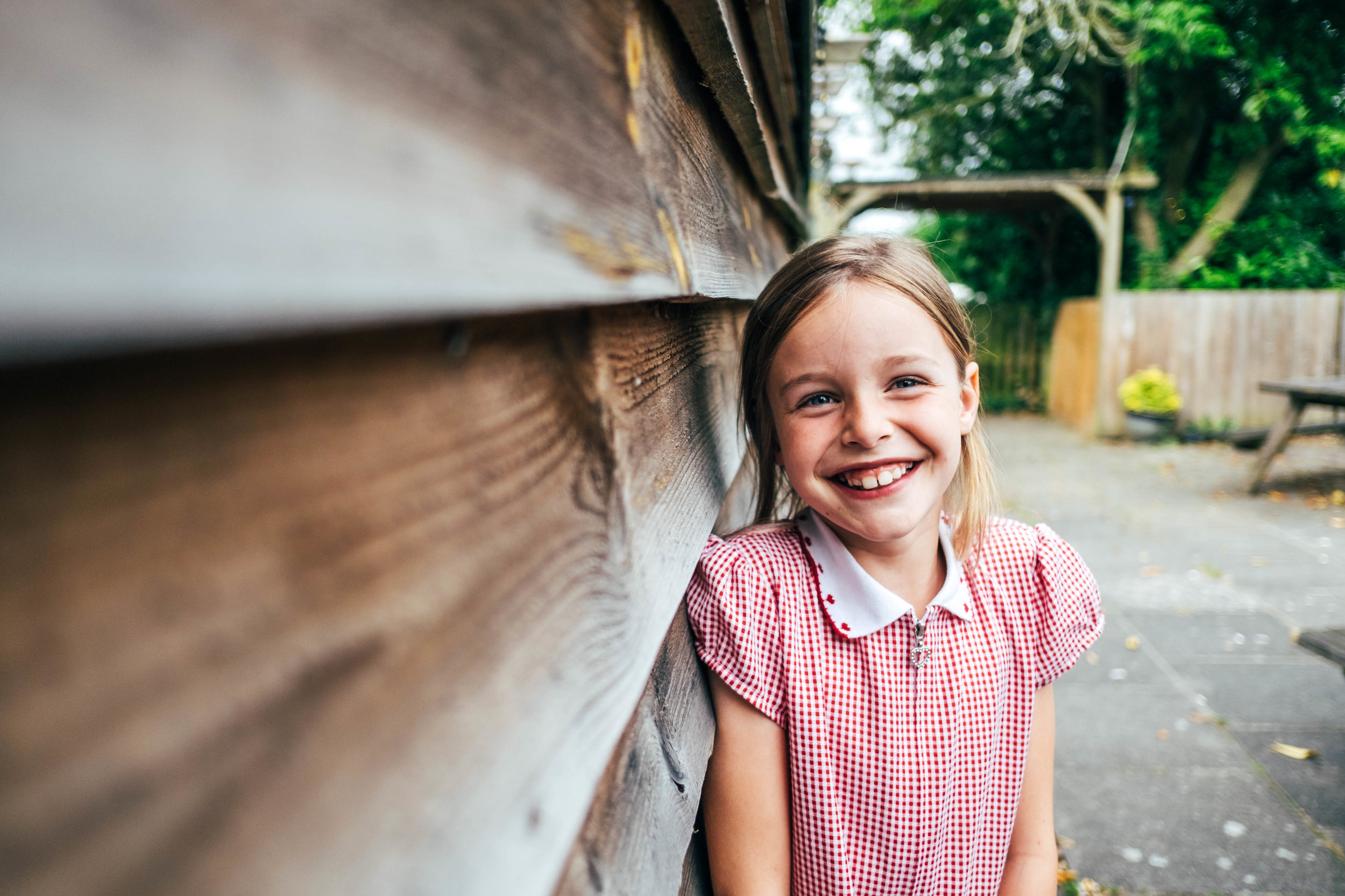 Little girl smiles in red check dress Essex Documentary Family and Wedding Photographer