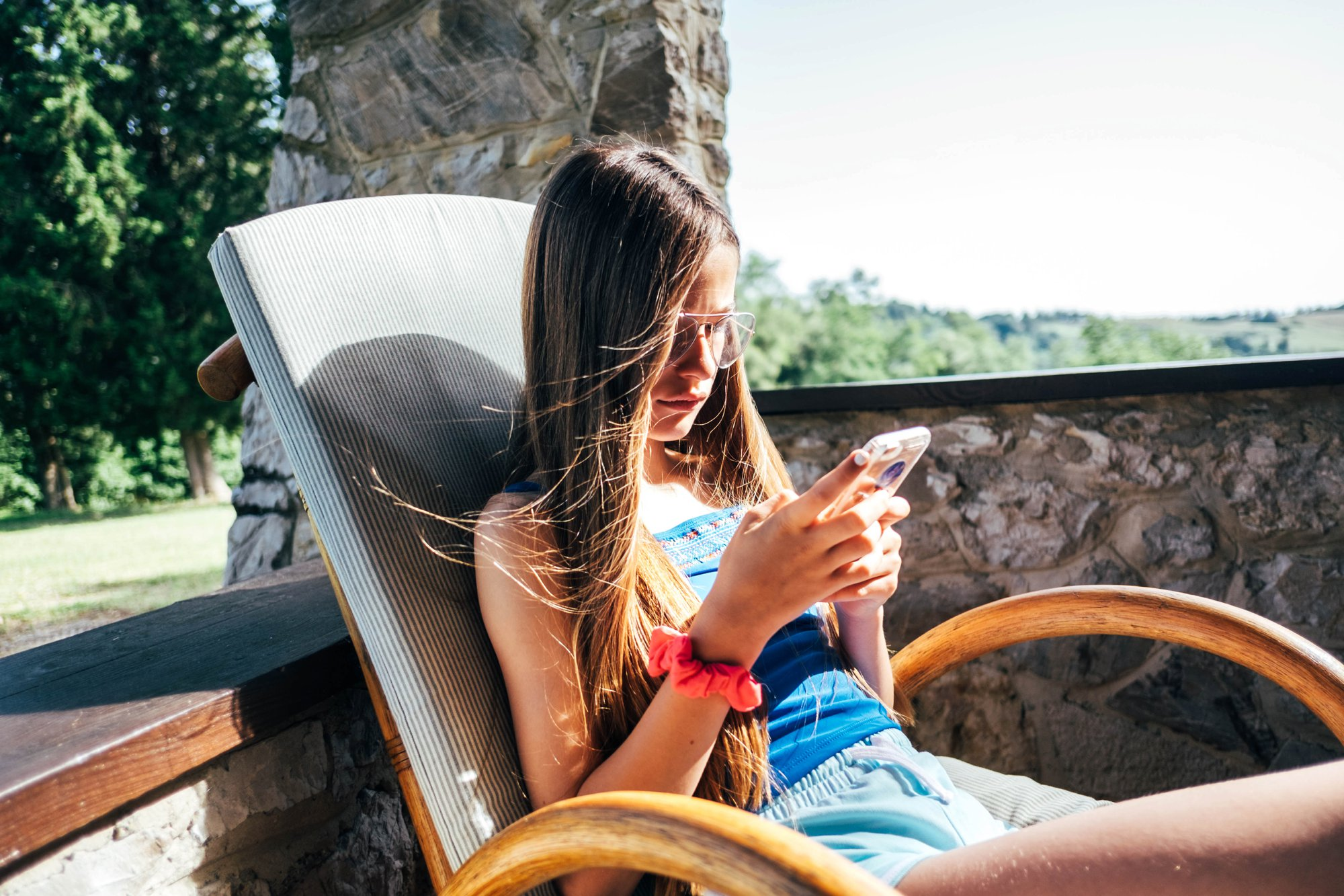 Tween girl sits on chair in sun in Tuscany Essex Documentary Wedding Travel Family Photographer