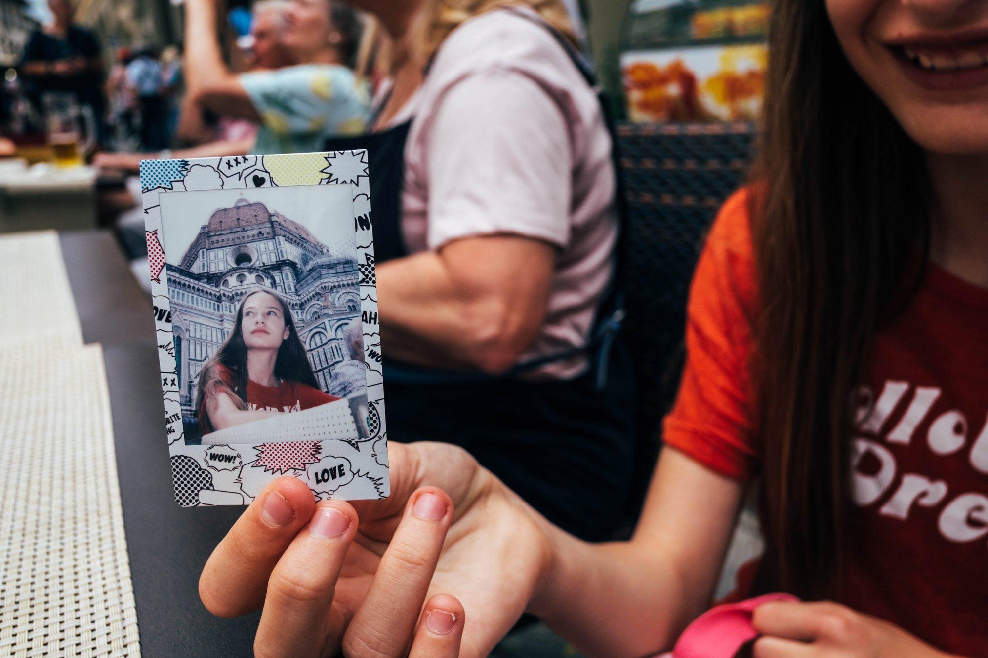 Girl holds up polaroid of photo of Duomo Florence Essex Documentary Travel Wedding Photographer