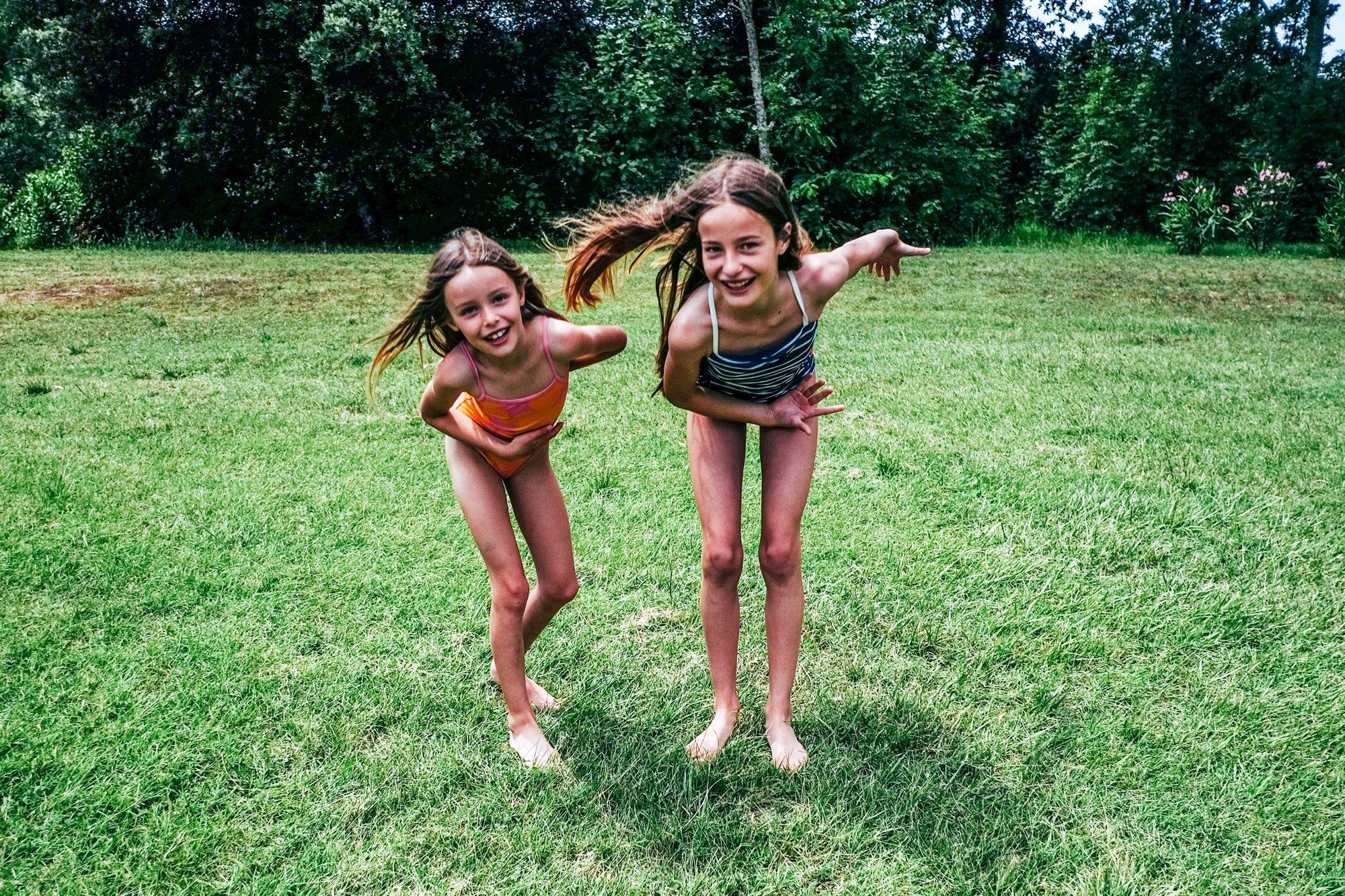 Sisters dancing in Tuscan garden Essex Documentary Wedding Travel Photographer