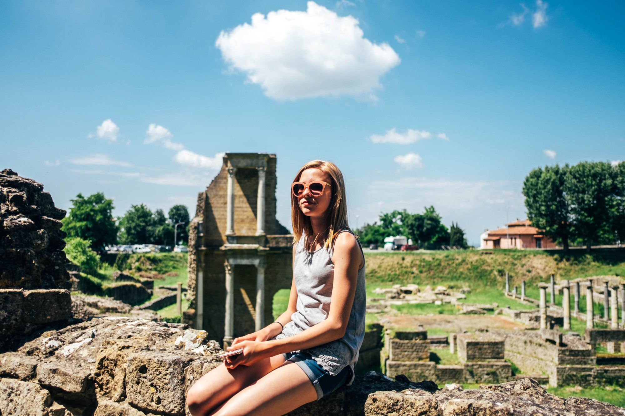 Teen girl sits on wall Roman ruins Volterra Essex Documentary Travel Family Photographer