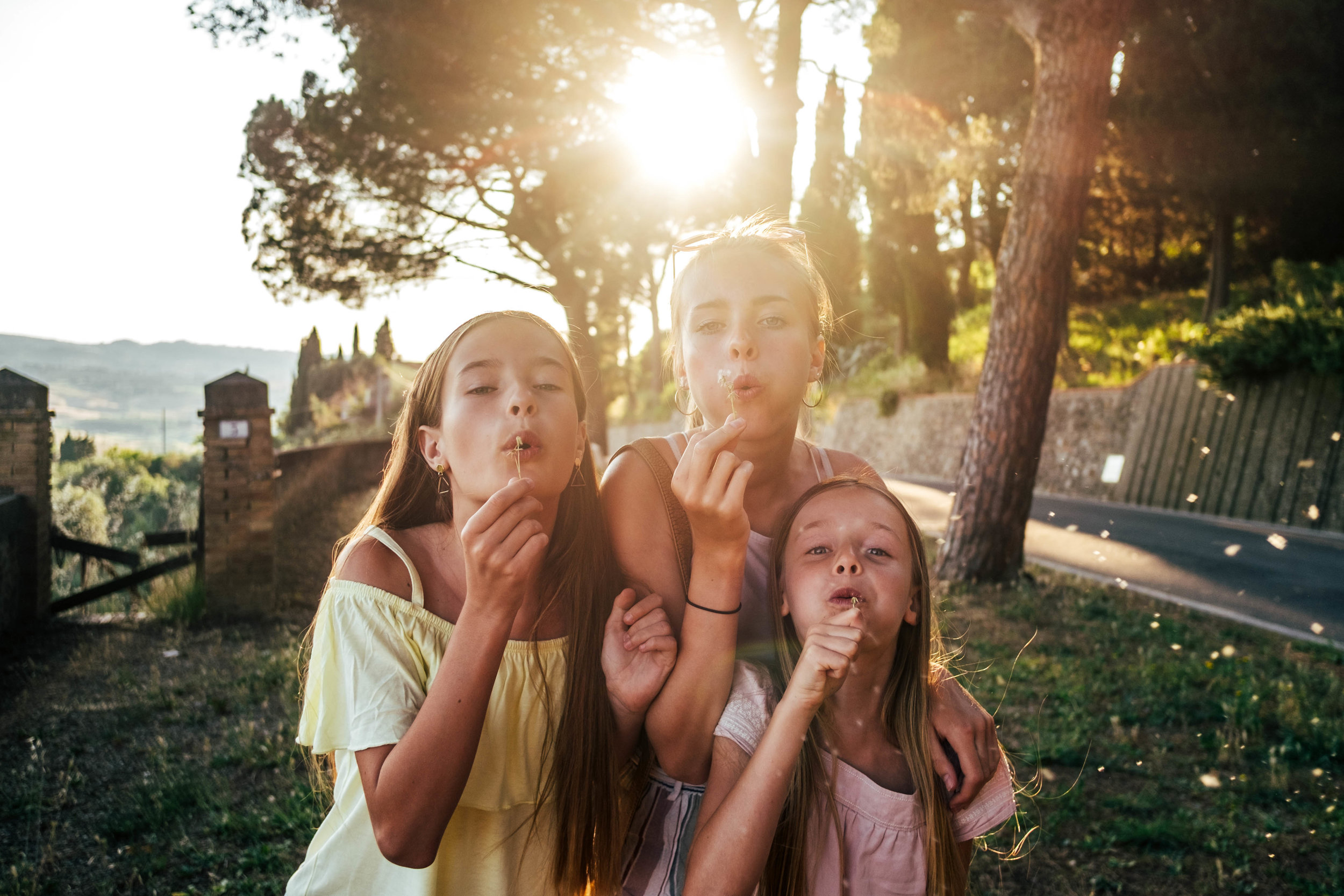 Three sisters blow dandelions at sunset Essex Documentary Family Wedding Photographer