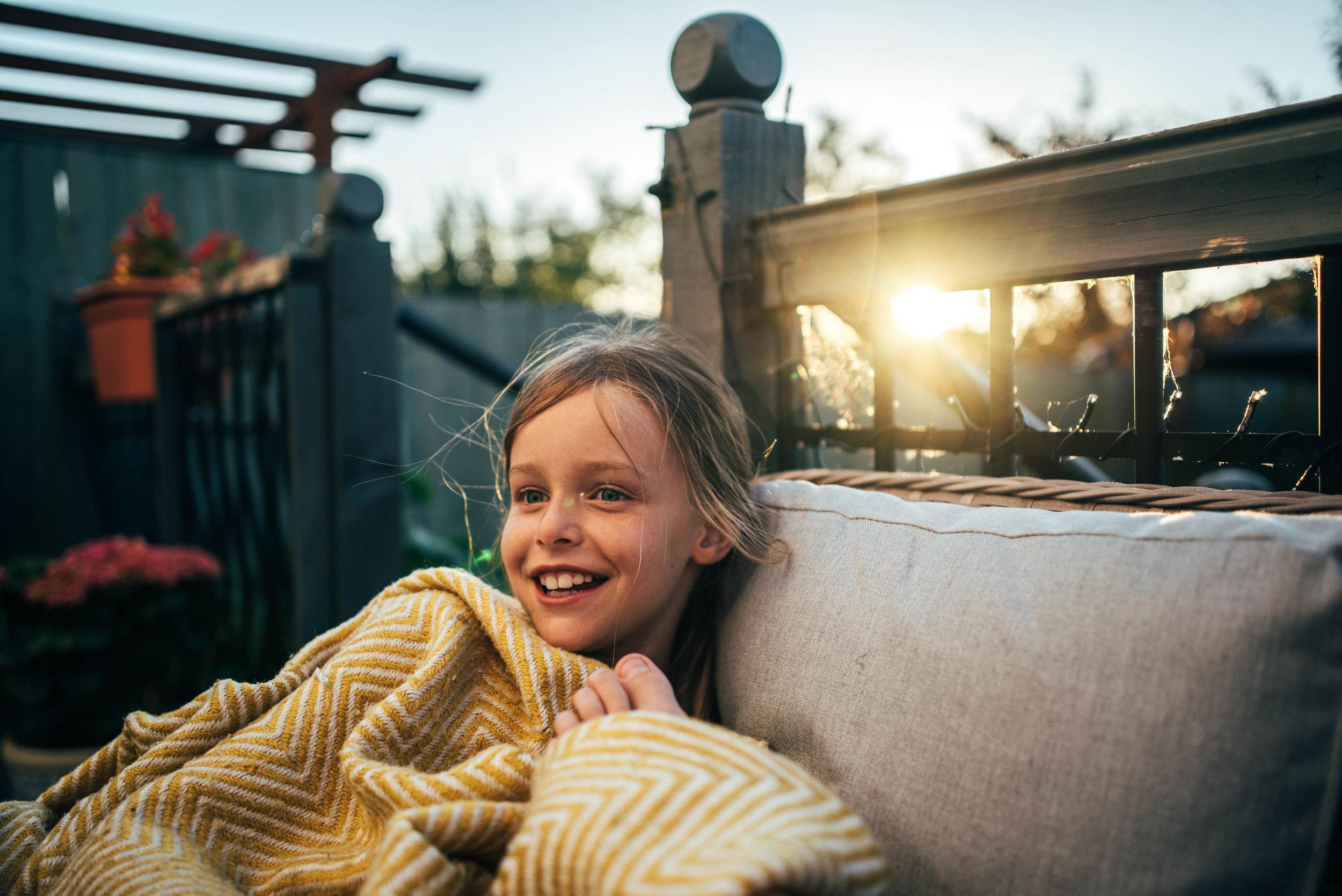 Girl under blanket at sunset