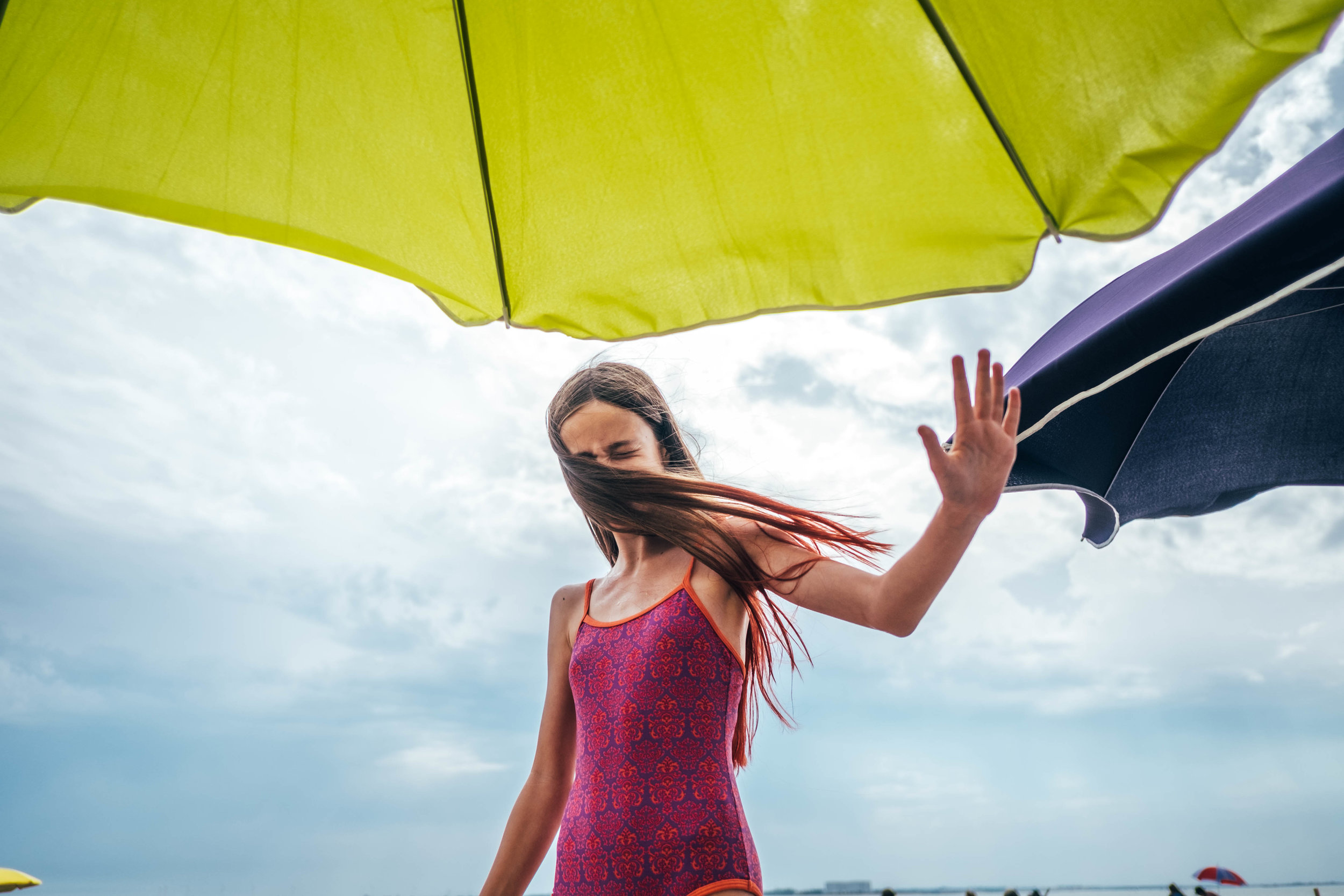 tween girl protects face on windswept beach