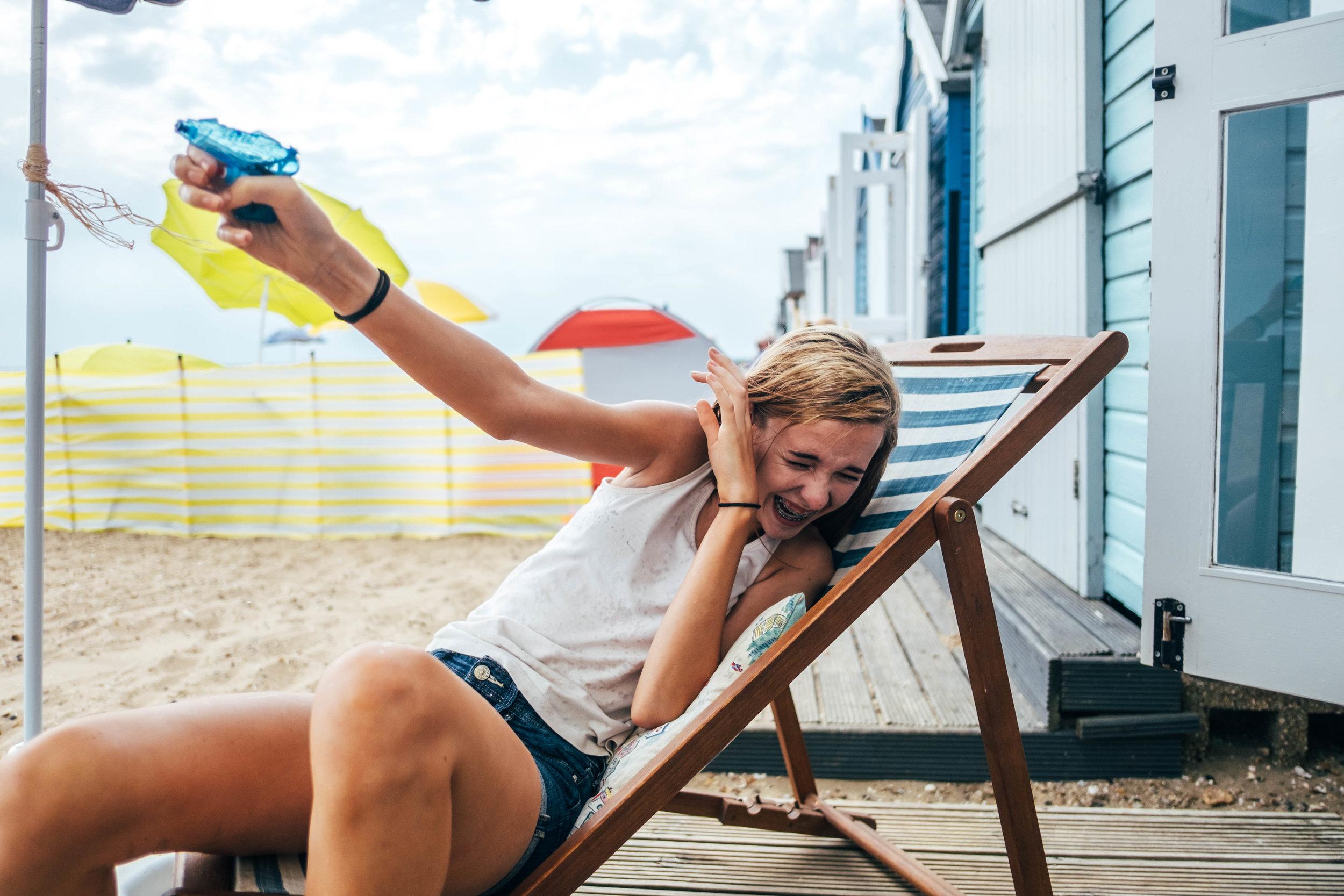 teen girl fires water gun in deck chair