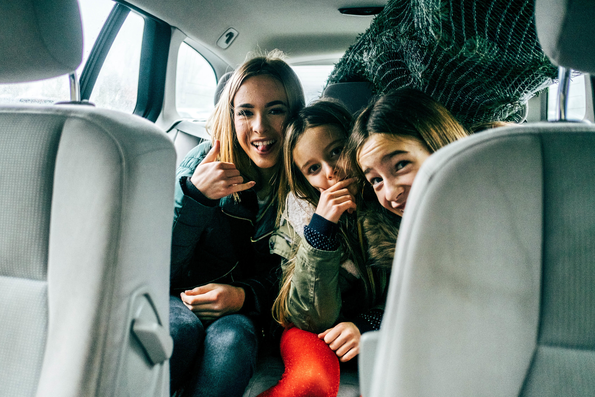 Three sisters squashed in car with Christmas tree Essex Documentary Family Wedding Photographer