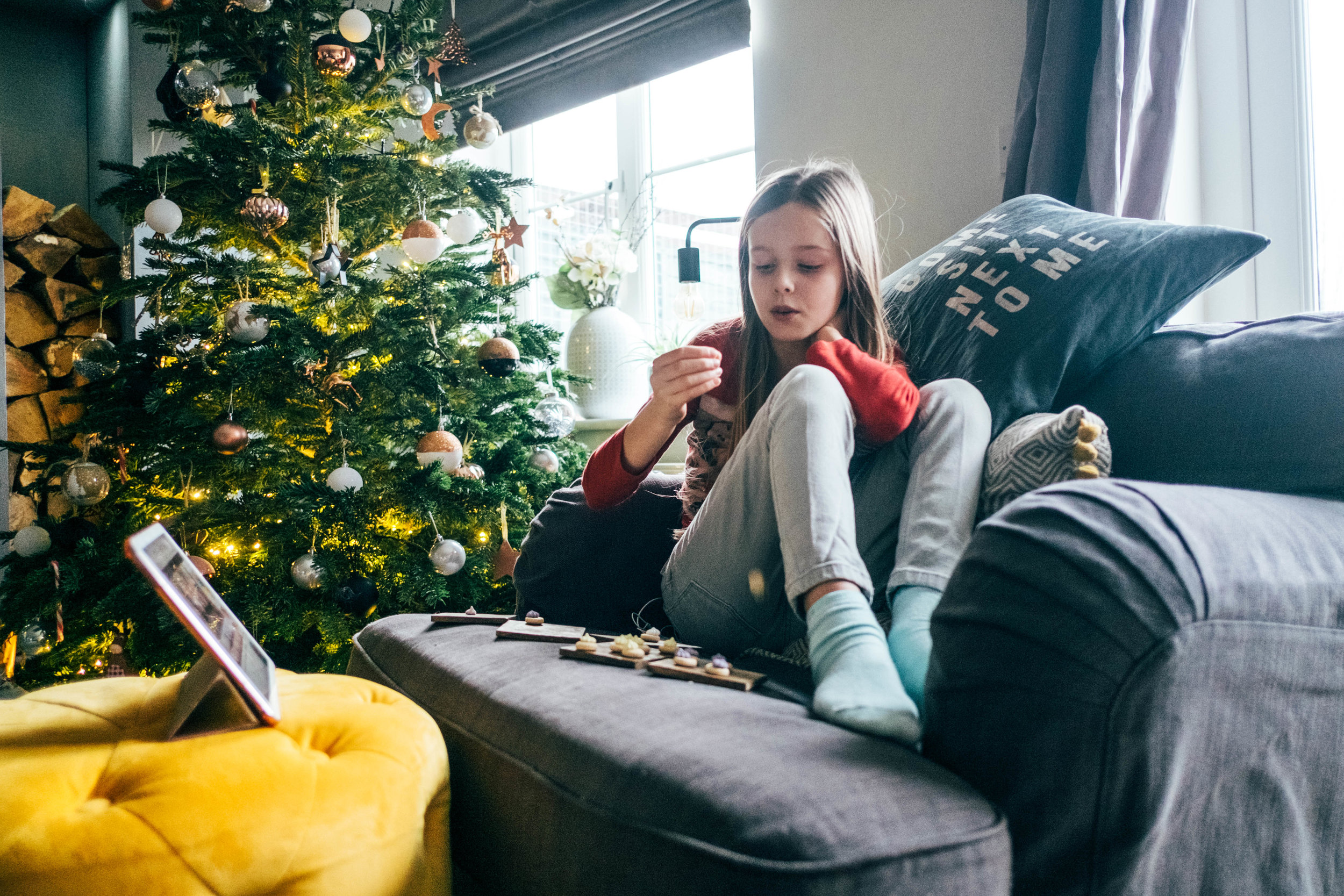 Little girl sits on chair by Christmas tree, Essex Documentary Wedding Family Photographer