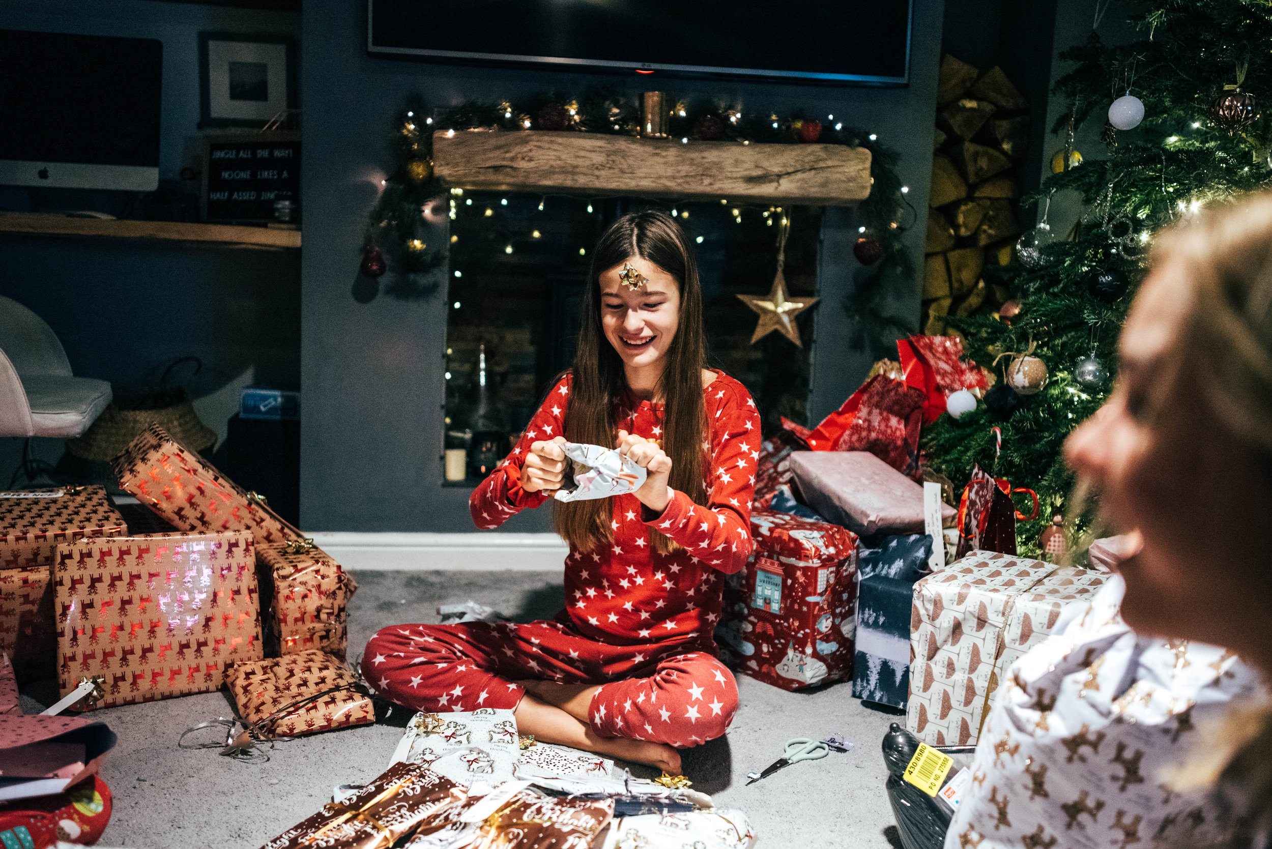 Tween girl opens Christmas present infront of fireplace Essex Documentary Wedding Family Photographer