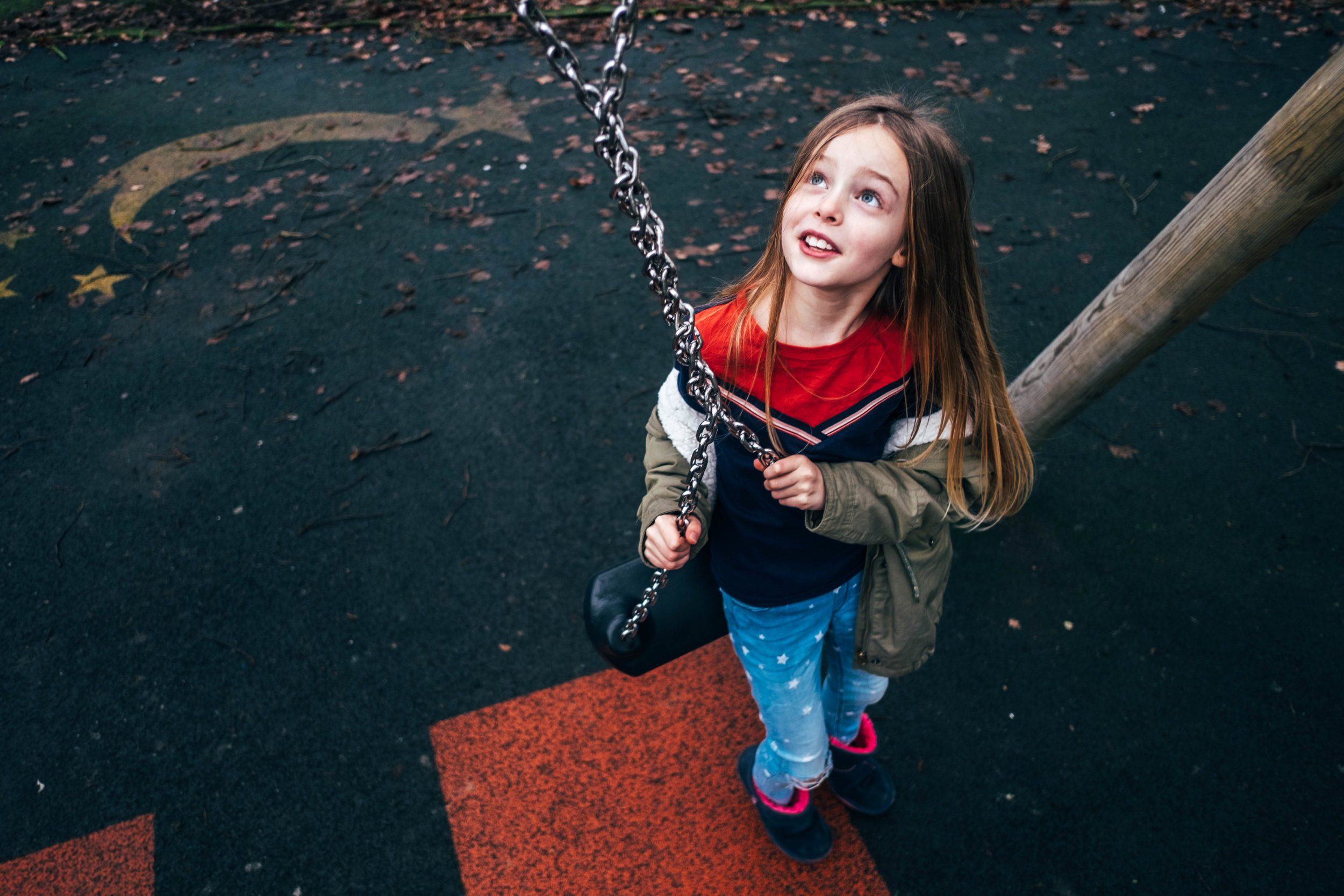 Girl looks up at twisted swing in park Essex Documentary Family Wedding Photographer