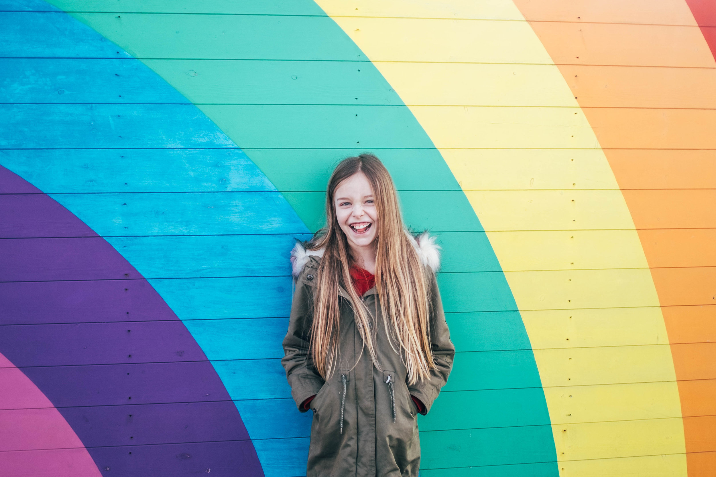 Little girl smiles agains rainbow wall Southend Pier Essex Documentary Wedding & Portrait Photographer