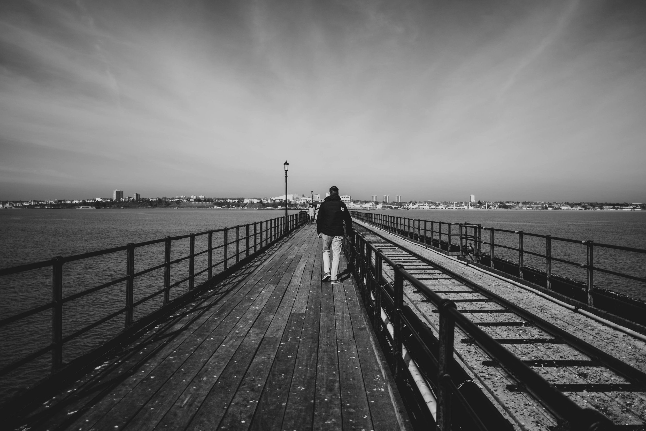 Man walks down Southend Pier Essex Documentary Wedding & Portrait Photographer