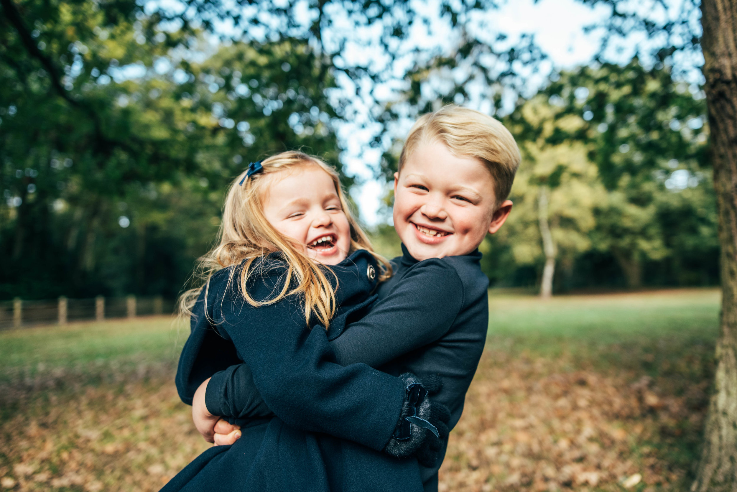 Brother and Sister hug and laugh in country Park Essex Family Portrait Photographer