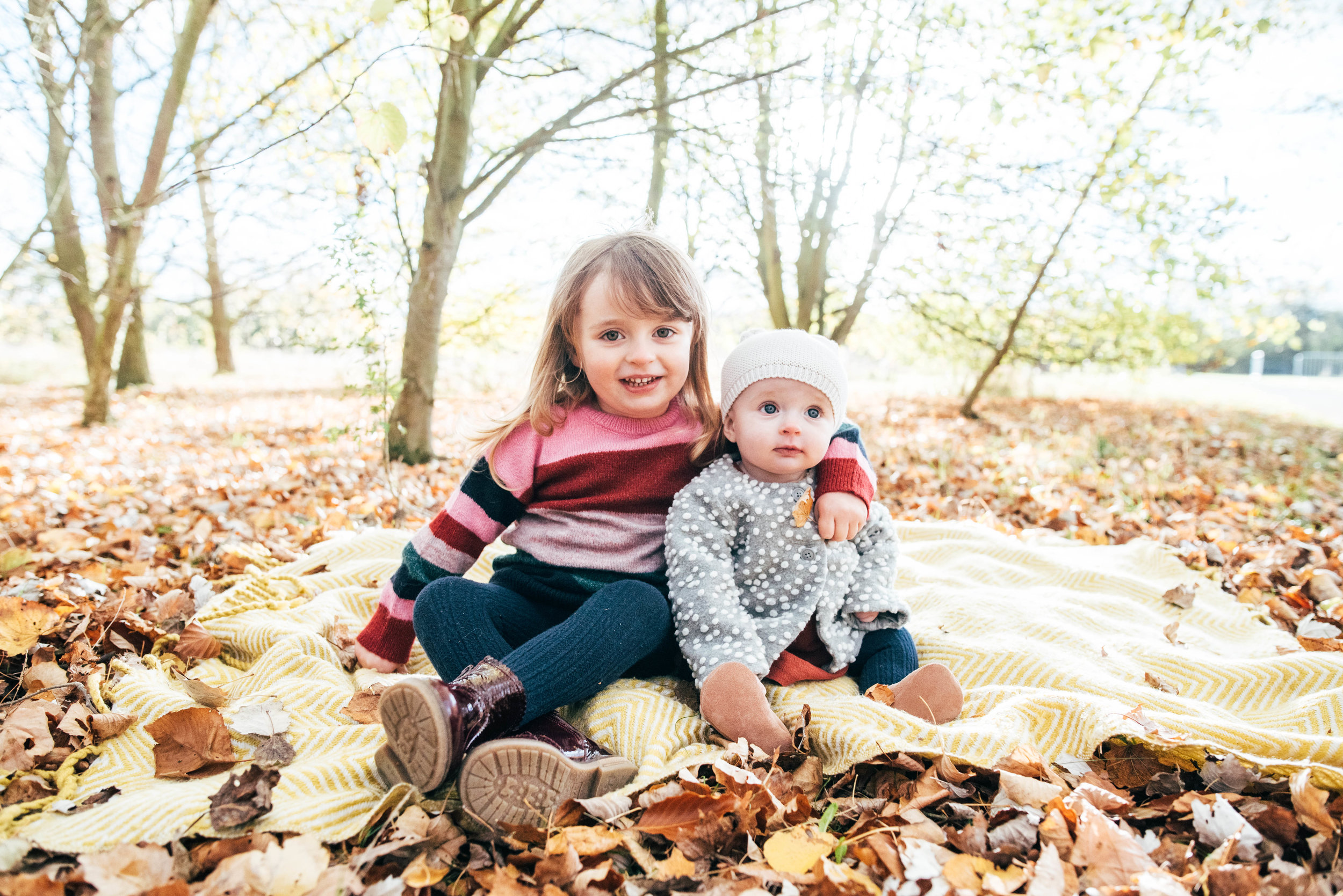 Little girl hugs her baby sister in Autumn leaves Essex Documentary Family Portrait Photographer