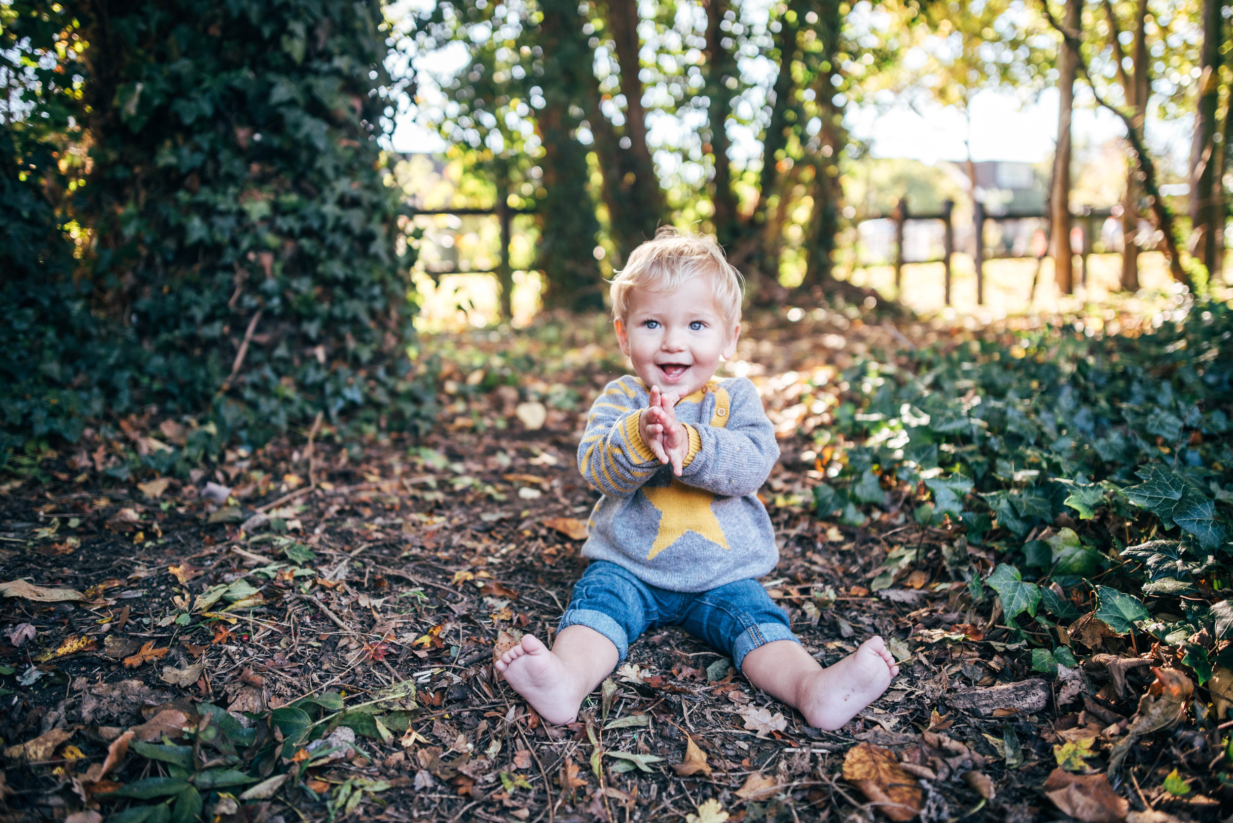 Baby boy sits in leaves in a clearing Essex Documentary Family Portrait Photographer