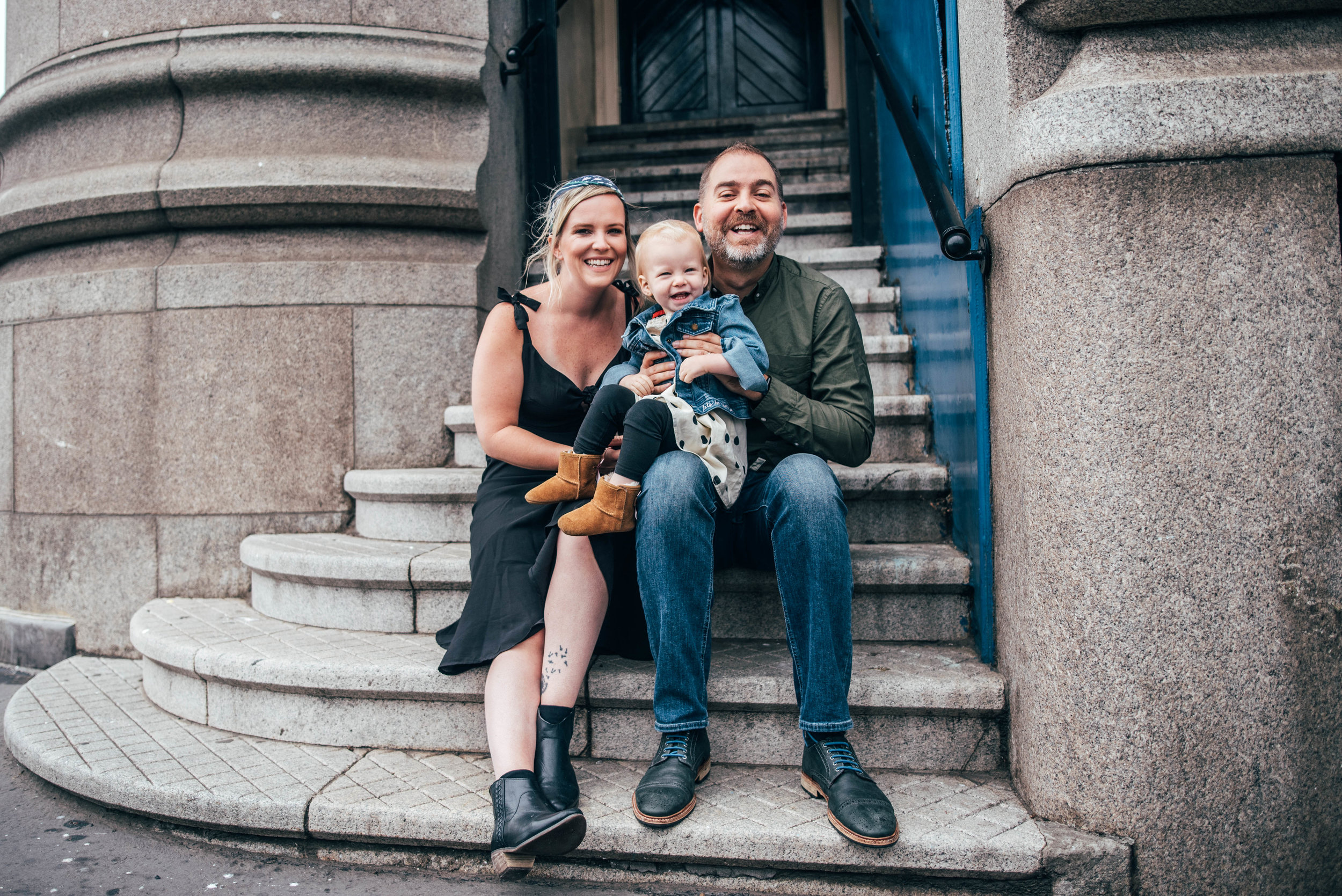 Mum Dad and baby girl sit on steps on Tower Bridge London Essex Documentary Family Portrait photographer
